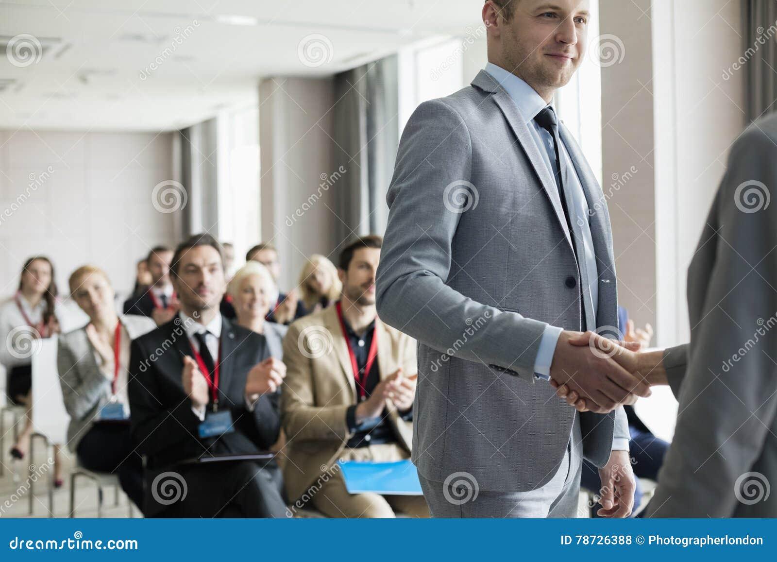 Affärsman som hälsar den offentliga högtalaren under seminarium