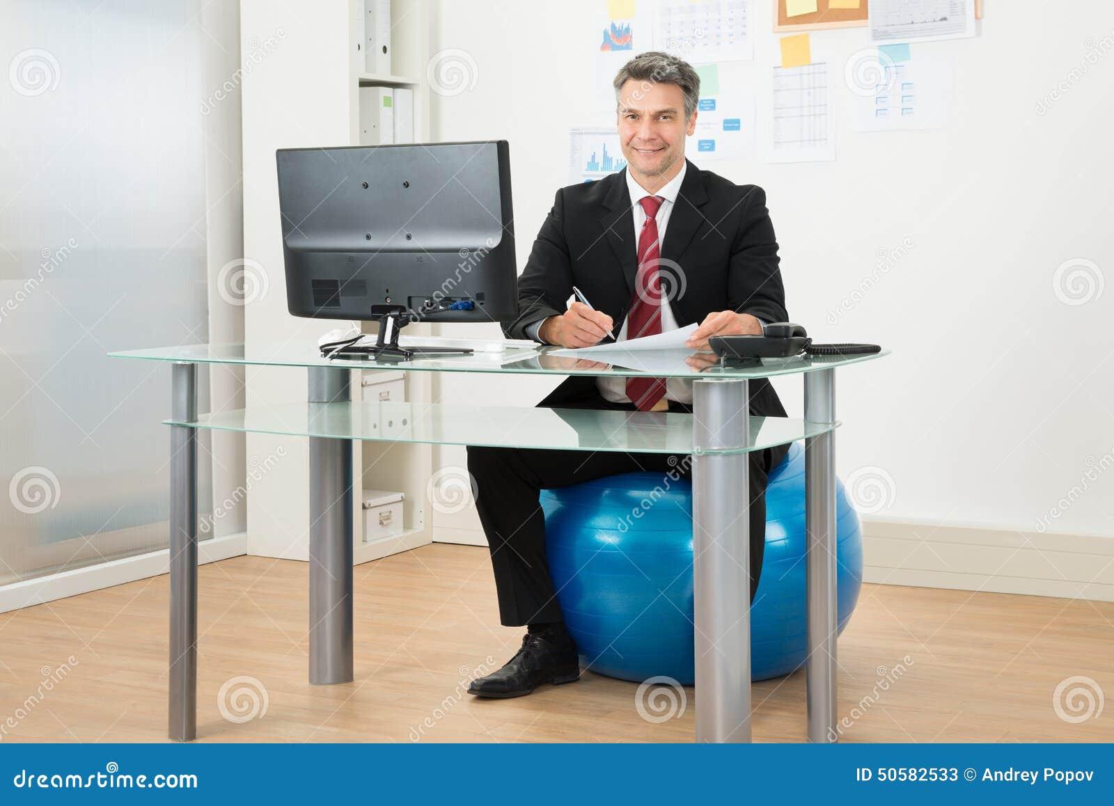 Affärsman Som I Regeringsställning Arbetar Att Sitta På Pilatesboll Fotografering för Bildbyråer