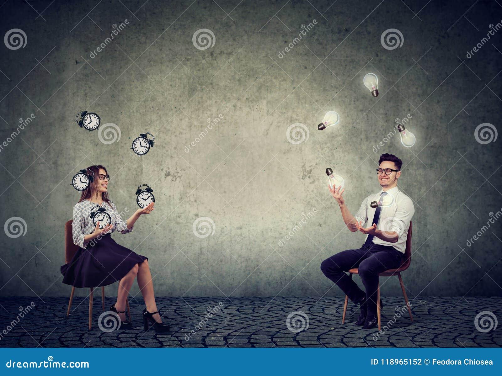 Affärsman som jonglerar med ljusa kulor för idé med affärskvinnan som klarar av tid och effektivitet