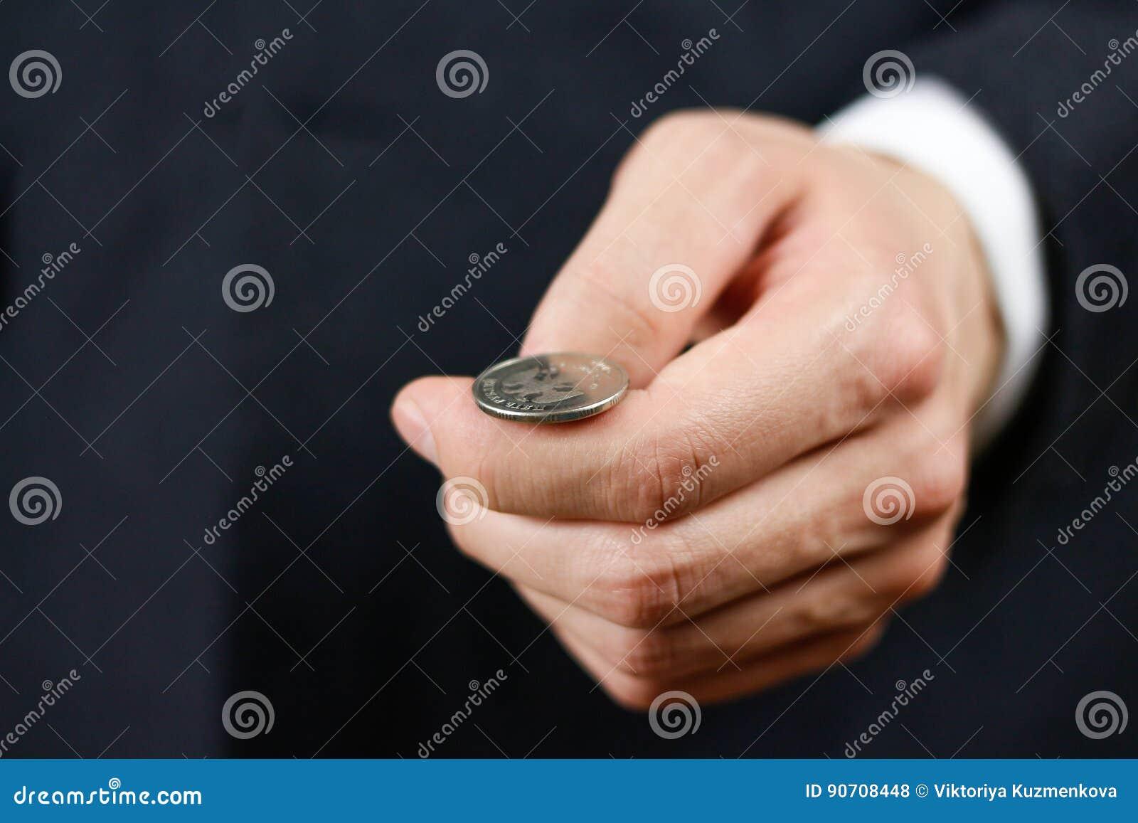 Affärsman som kastar ett mynt heads svanar close upp