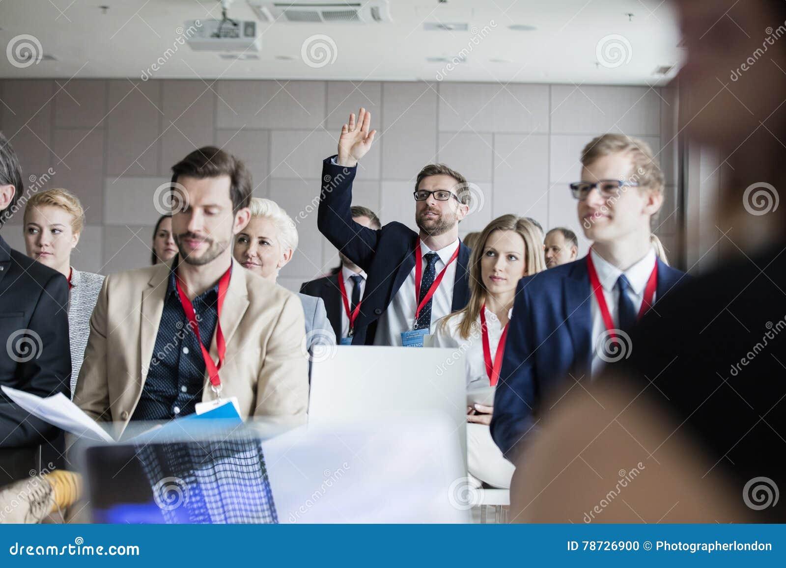 Affärsman som lyfter handen under seminarium