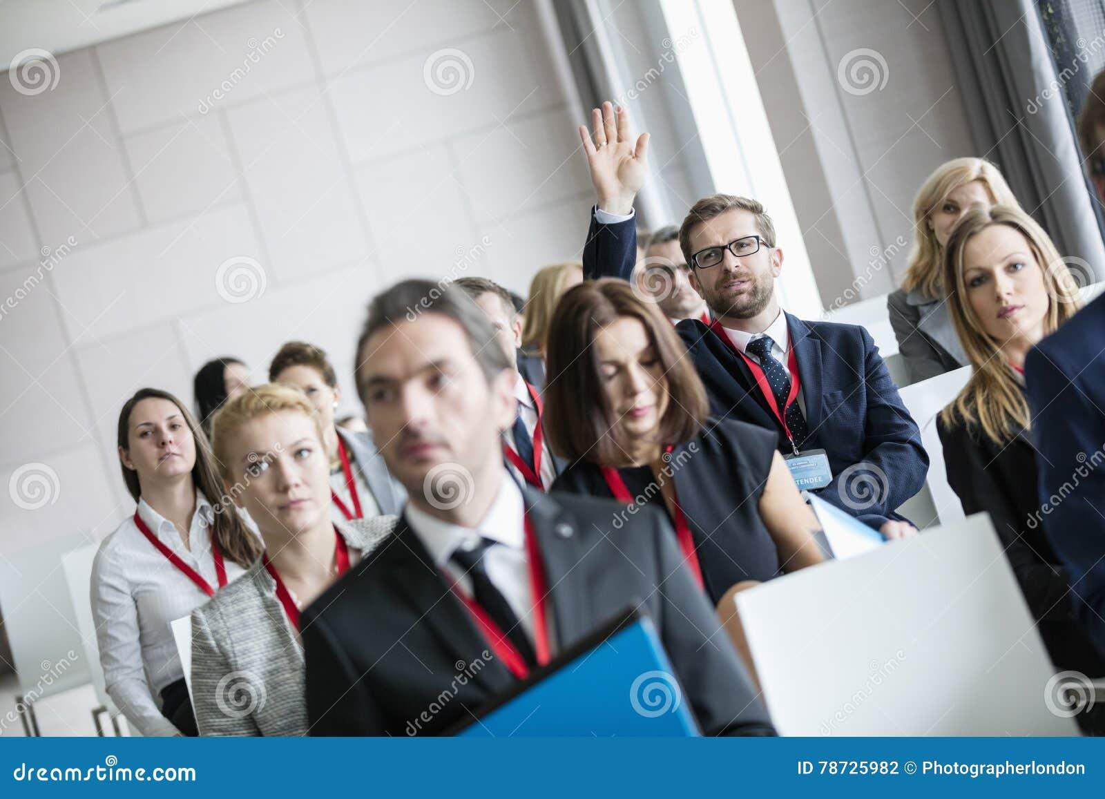 Affärsman som lyfter handen under seminarium på konventcentret