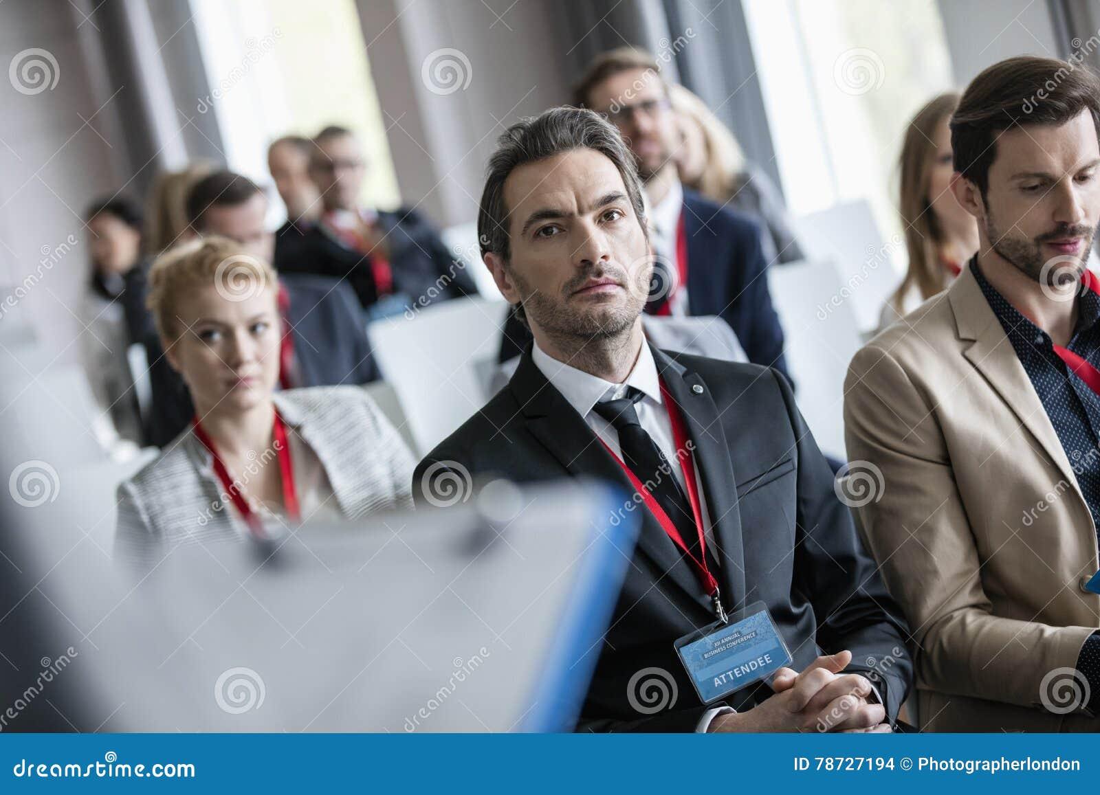 Affärsman som lyssnar till presentationen under seminarium