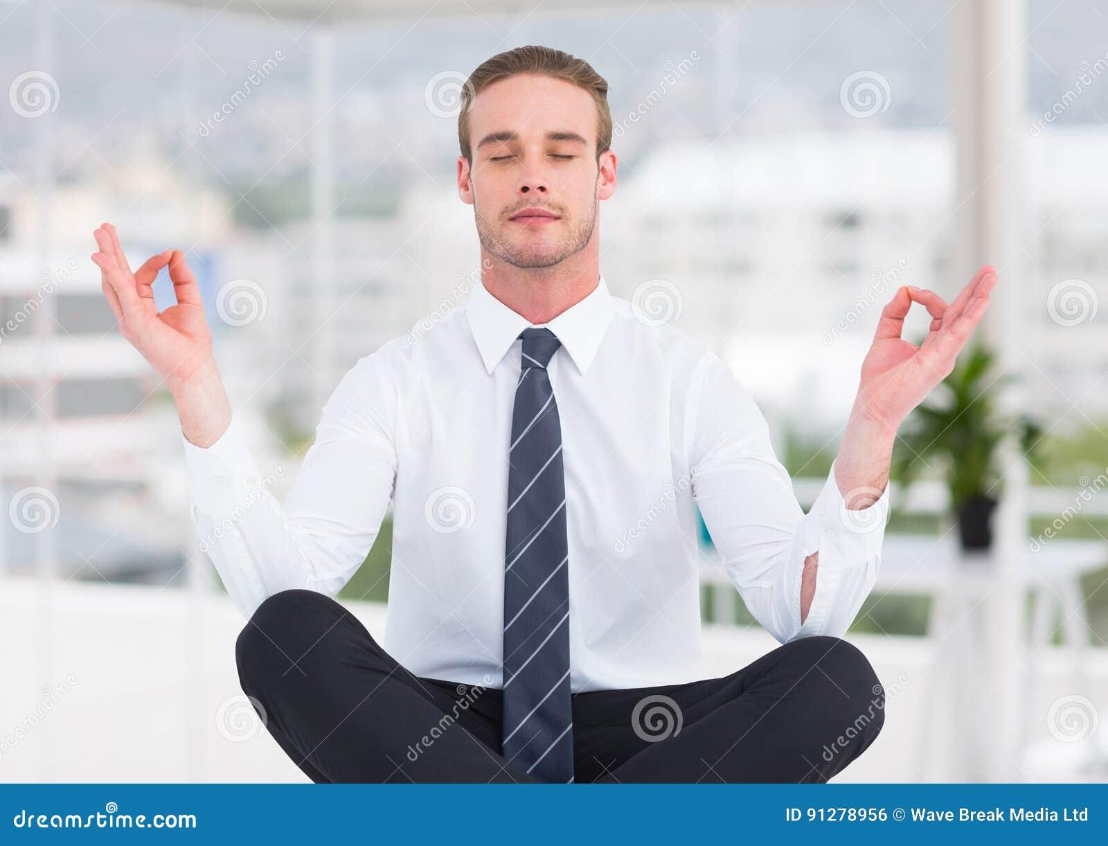 Affärsman som mediterar i oskarpt kontor