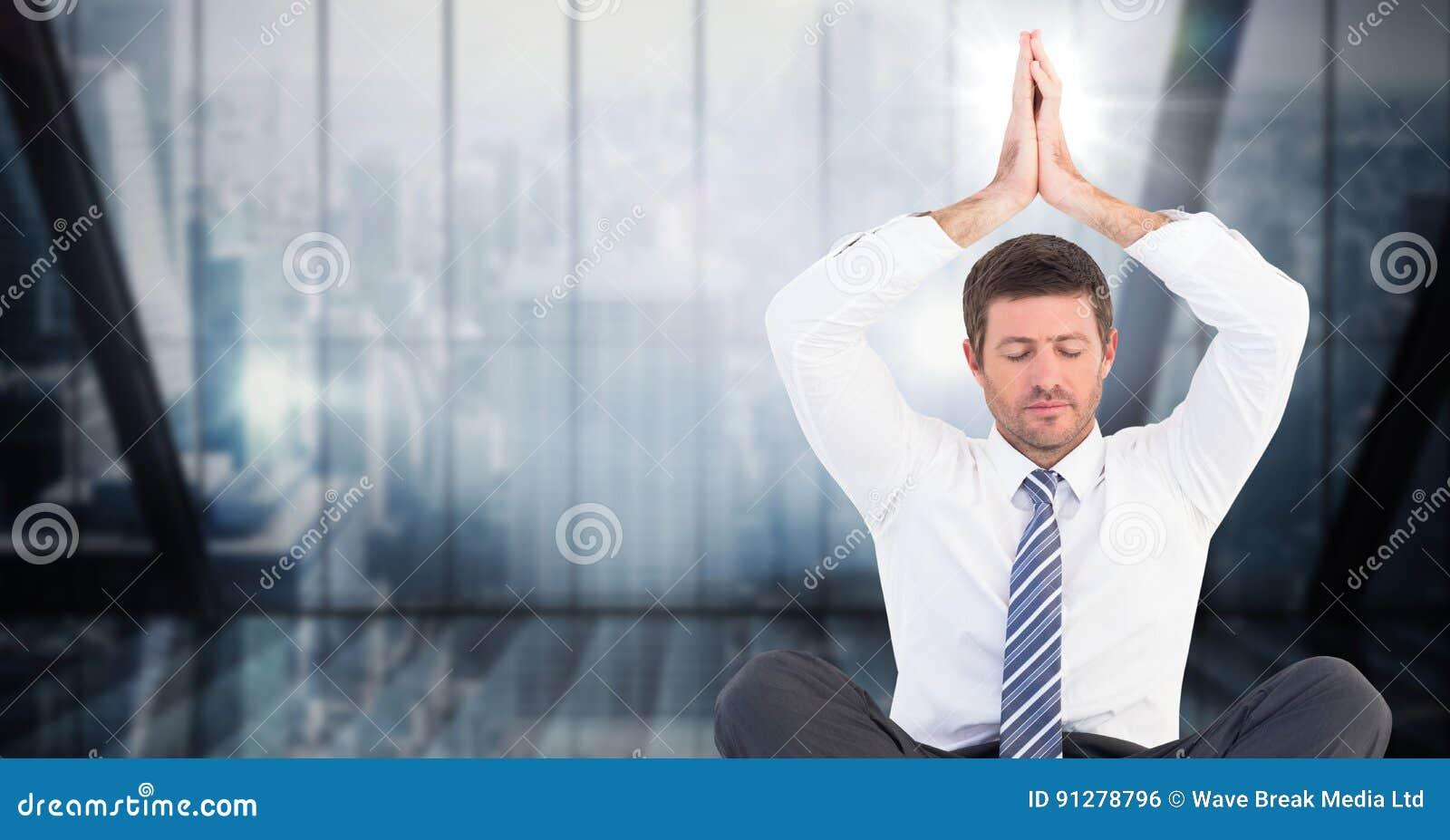 Affärsman som mediterar med händer som är över huvudet mot mörker - blått oskarpt fönster