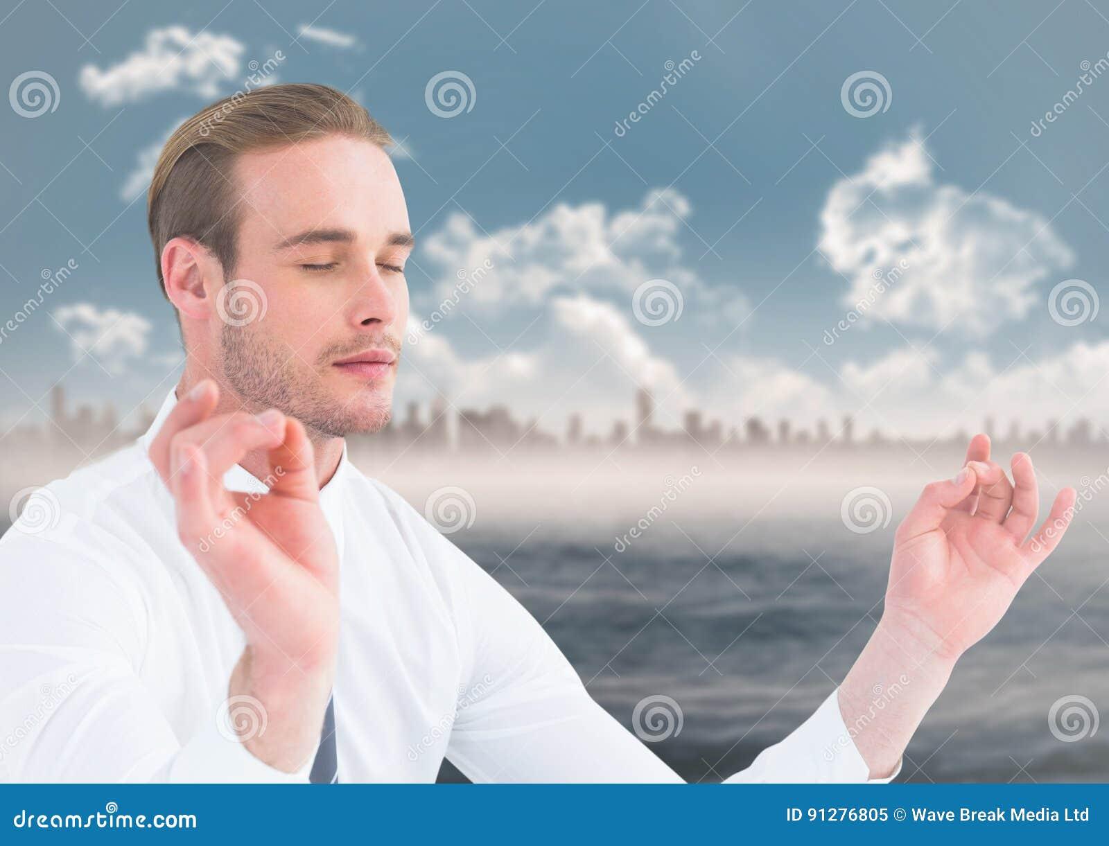 Affärsman som mediterar mot vatten och horisont