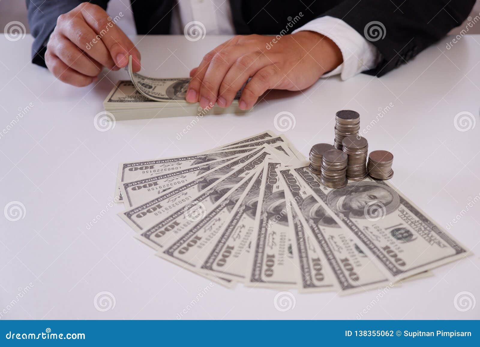 Affärsman som räknar pengar med mynt och pengar över skrivbordet