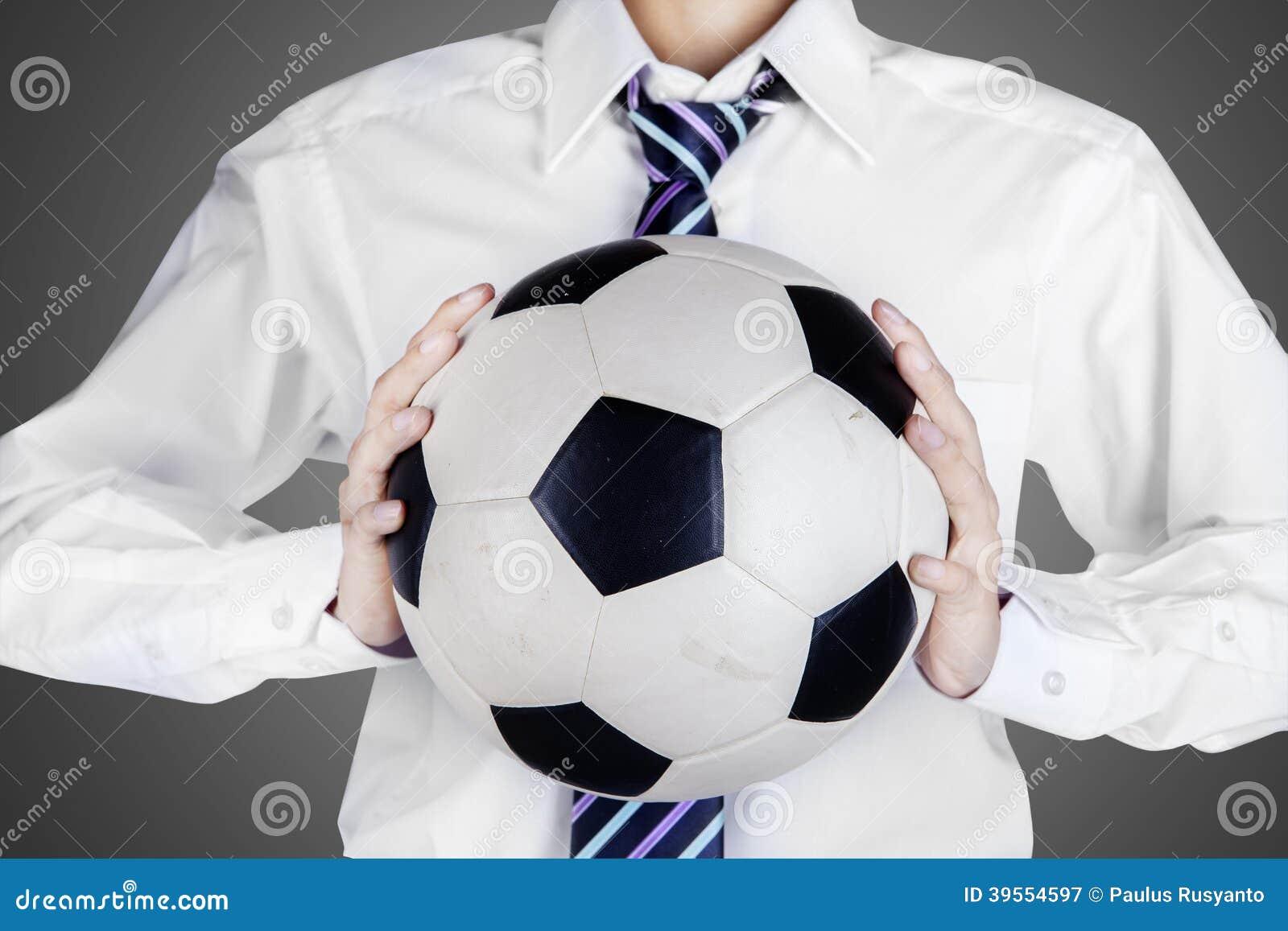 Affärsman som rymmer en fotbollboll