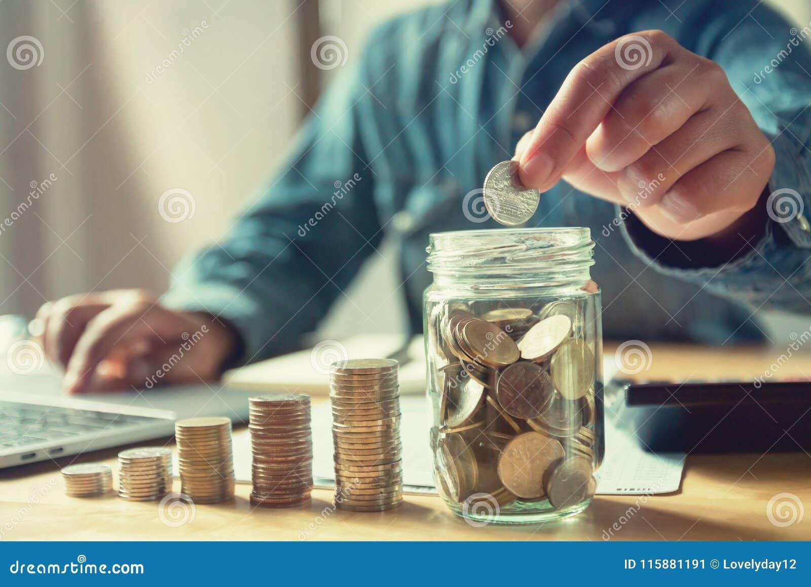 Affärsman som sätter mynt in i tillbringareexponeringsglas sparande pengar för begrepp