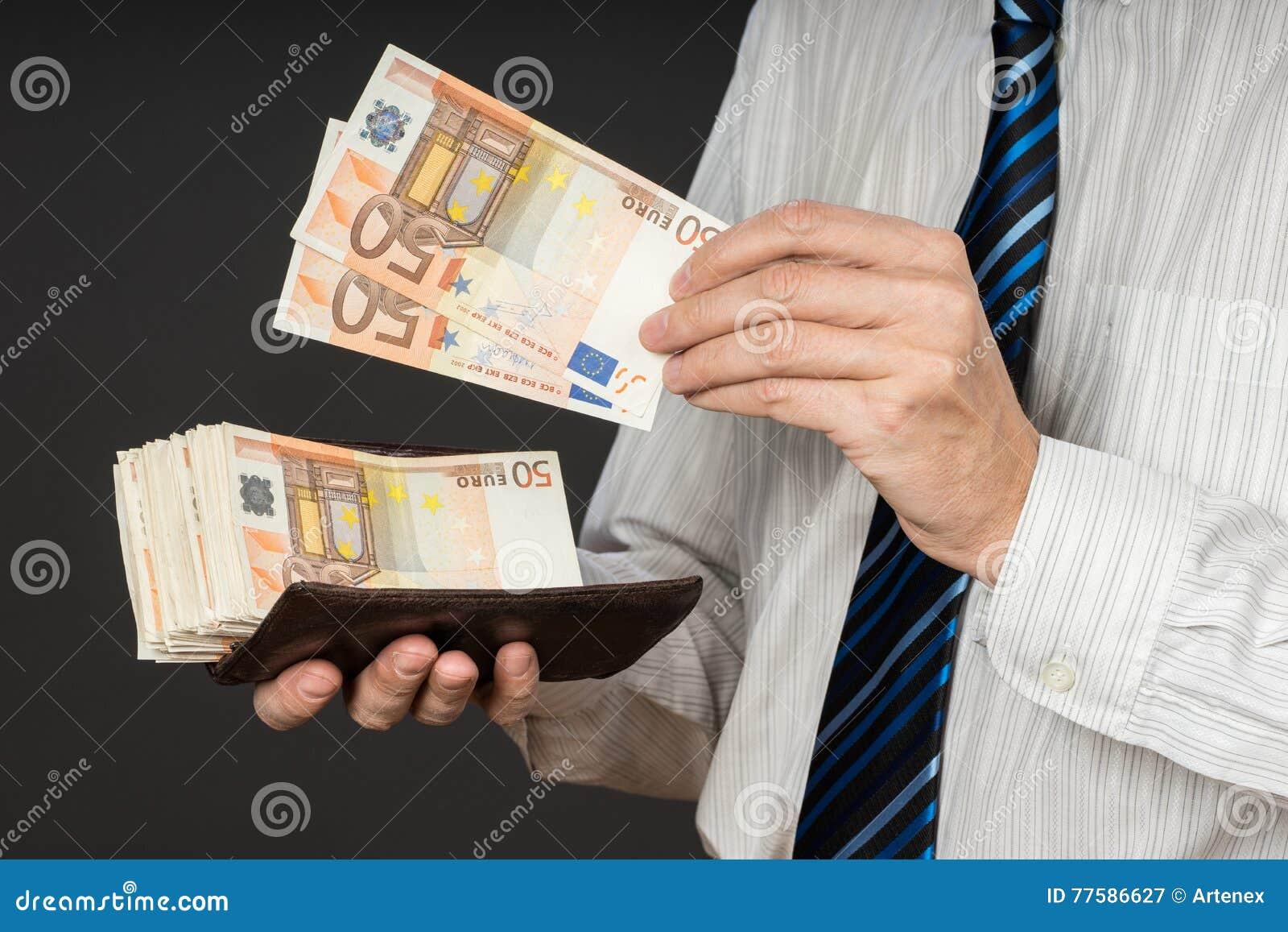 Affärsman som sätter sedlar i hans plånbok Bunt av femtio euro pengar Affärsmannen är hållande kassa Personlöner i euroräkningar