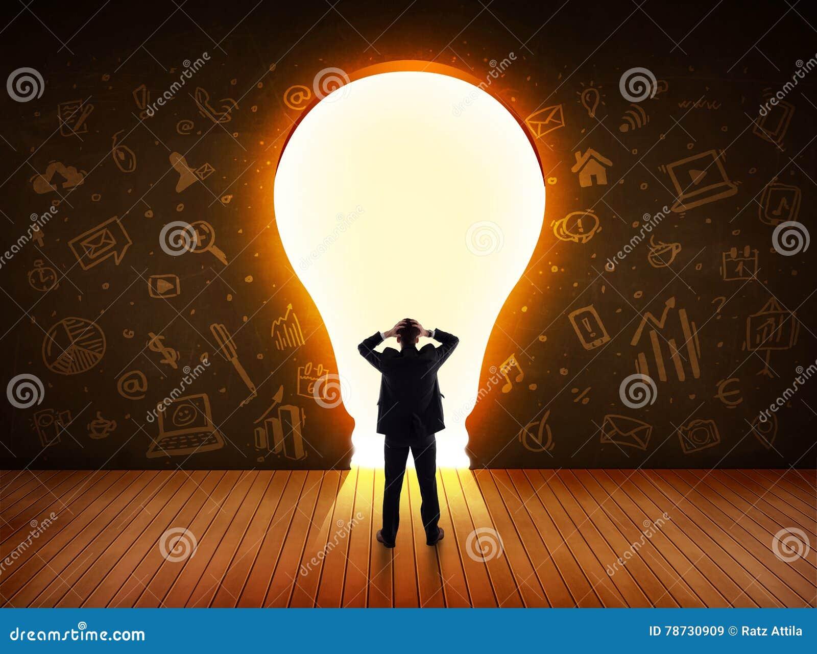 Affärsman som ser den ljusa ljusa kulan i väggen