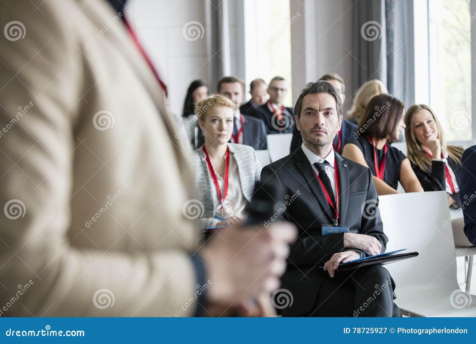 Affärsman som ser den offentliga högtalaren under seminarium