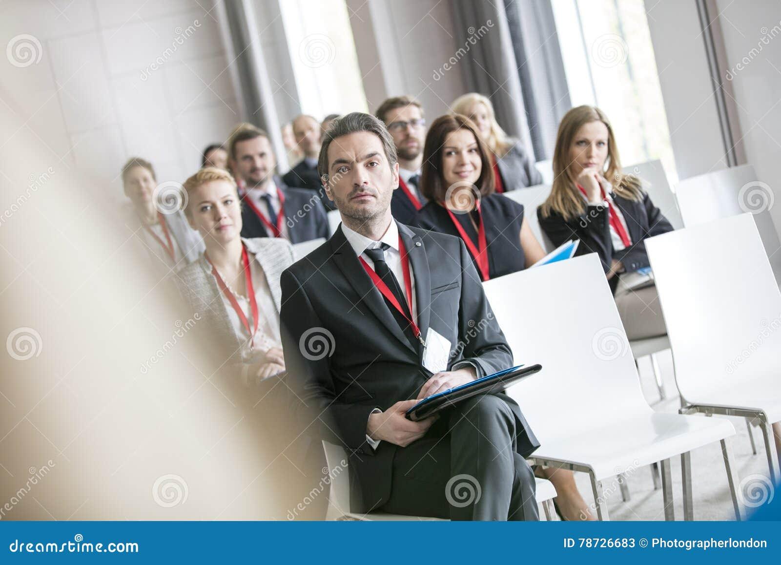 Affärsman som ser den offentliga högtalaren under seminarium i konventcentrum