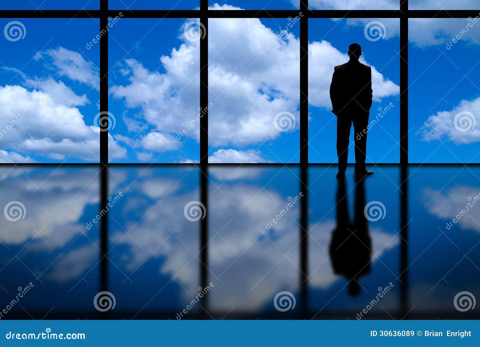 Affärsman som ser ut ur högt löneförhöjningkontorsfönster på blå himmel och moln