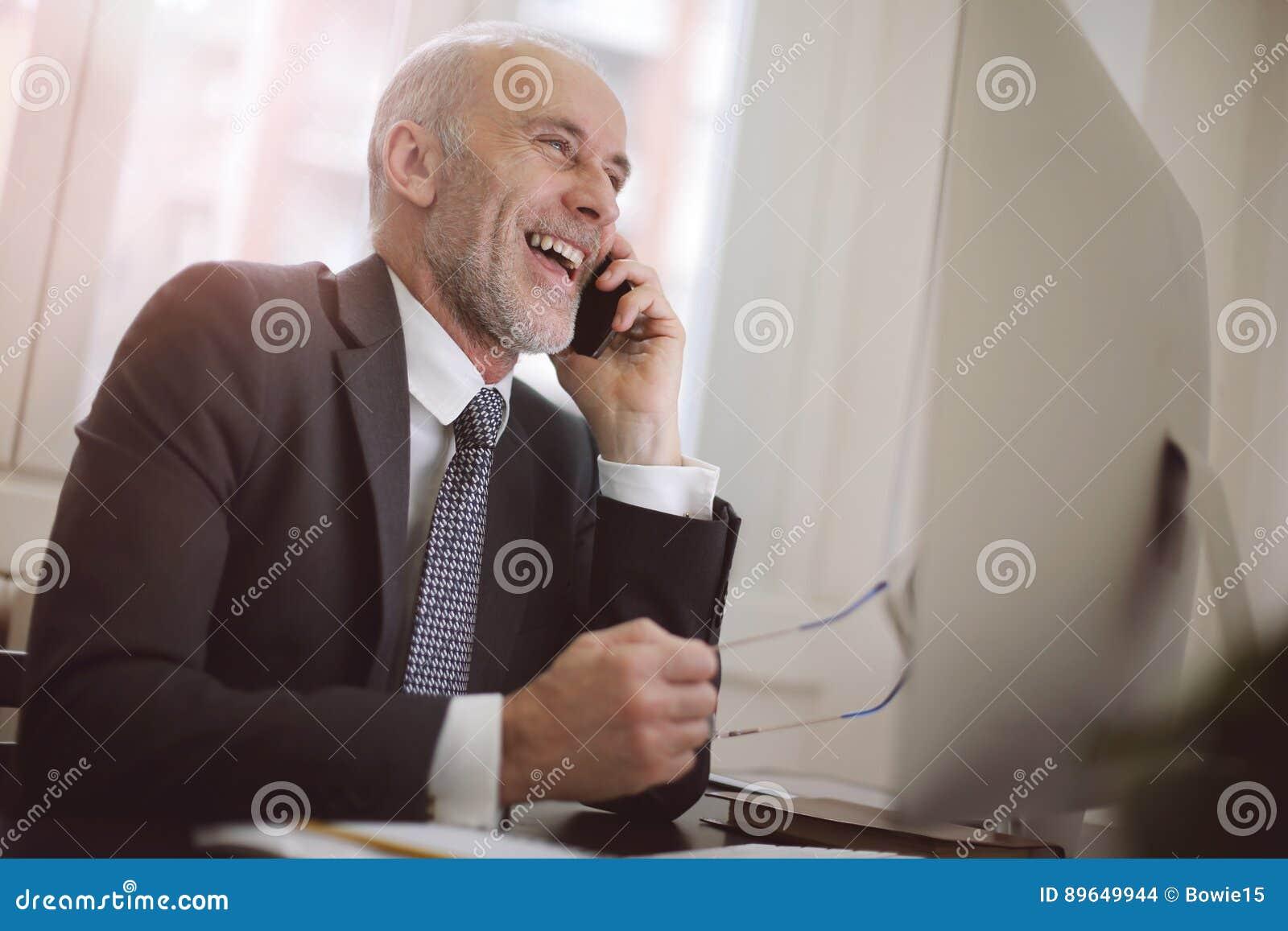 Affärsman som skrattar på ringa