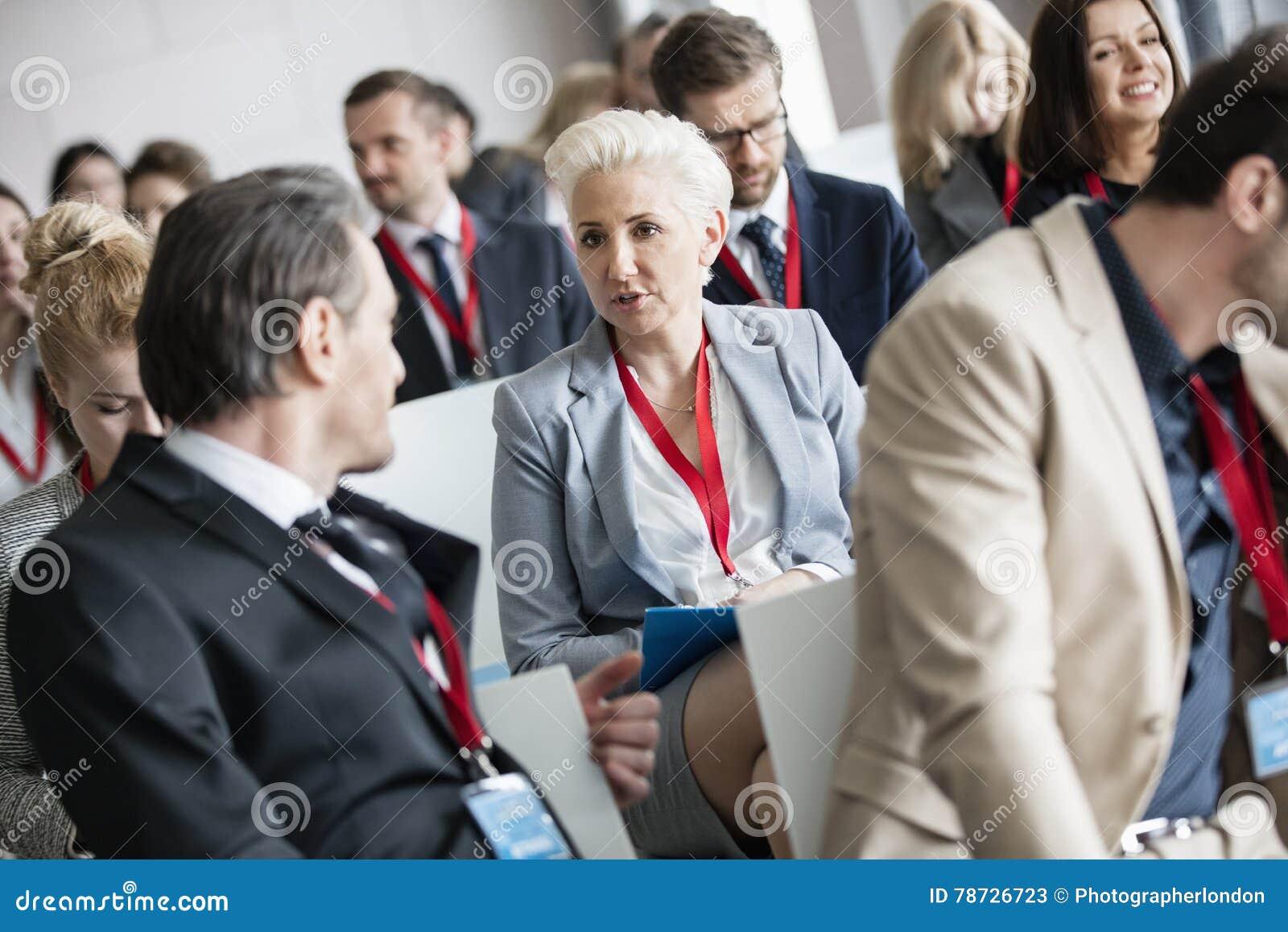 Affärsman som talar till affärskvinnan i seminariumkorridor på konventcentret