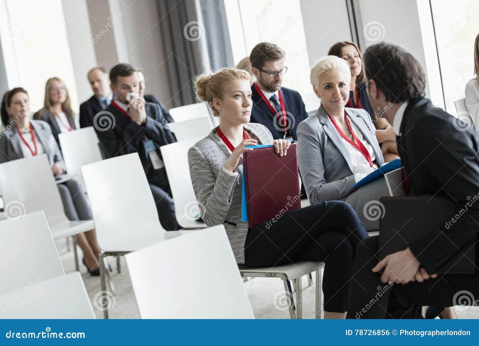 Affärsman som talar till affärskvinnor i seminariumkorridor