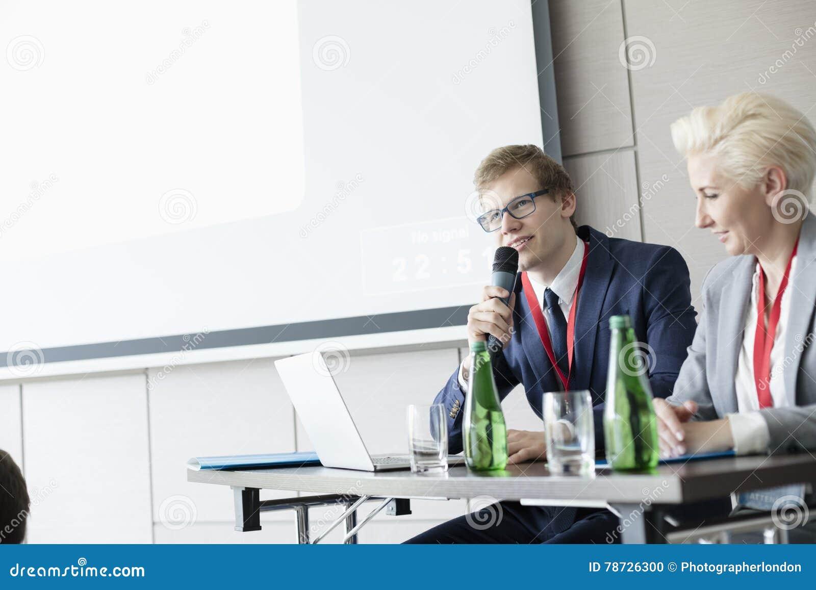 Affärsman som talar till och med mikrofonen, medan sitta på skrivbordet i konventcentrum