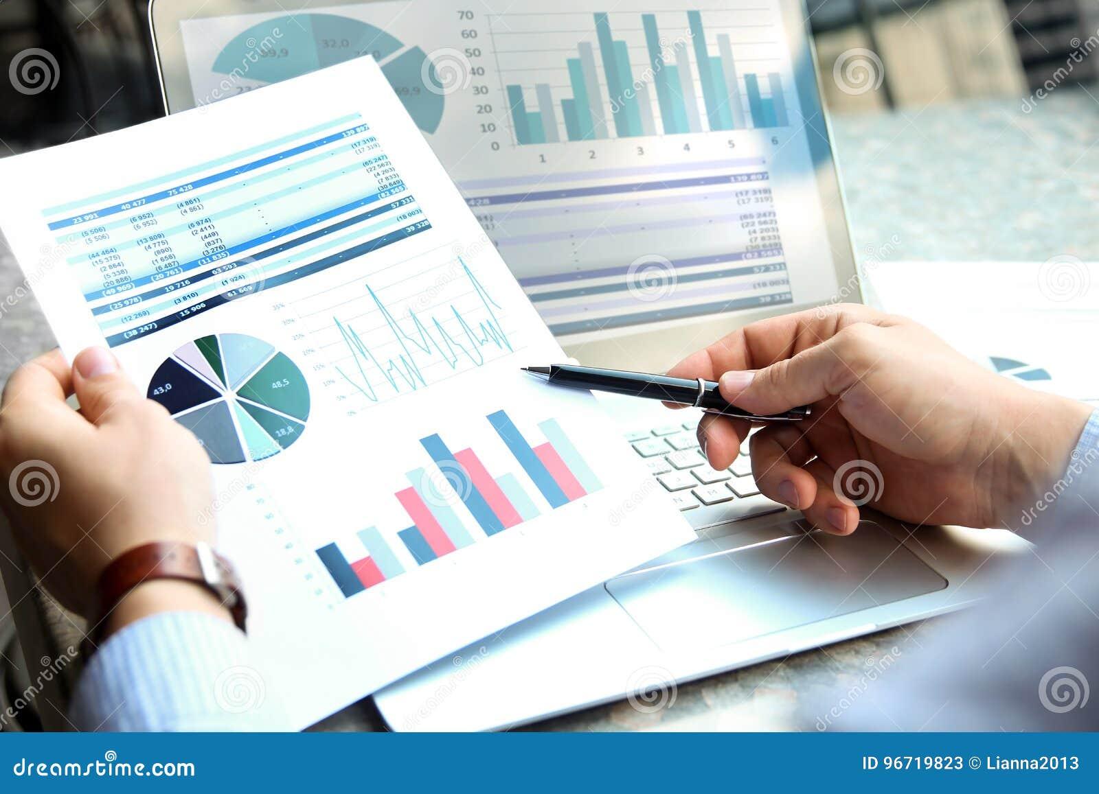 Affärsman som utanför arbetar och analyserar finansiella diagram på grafer på en bärbar dator