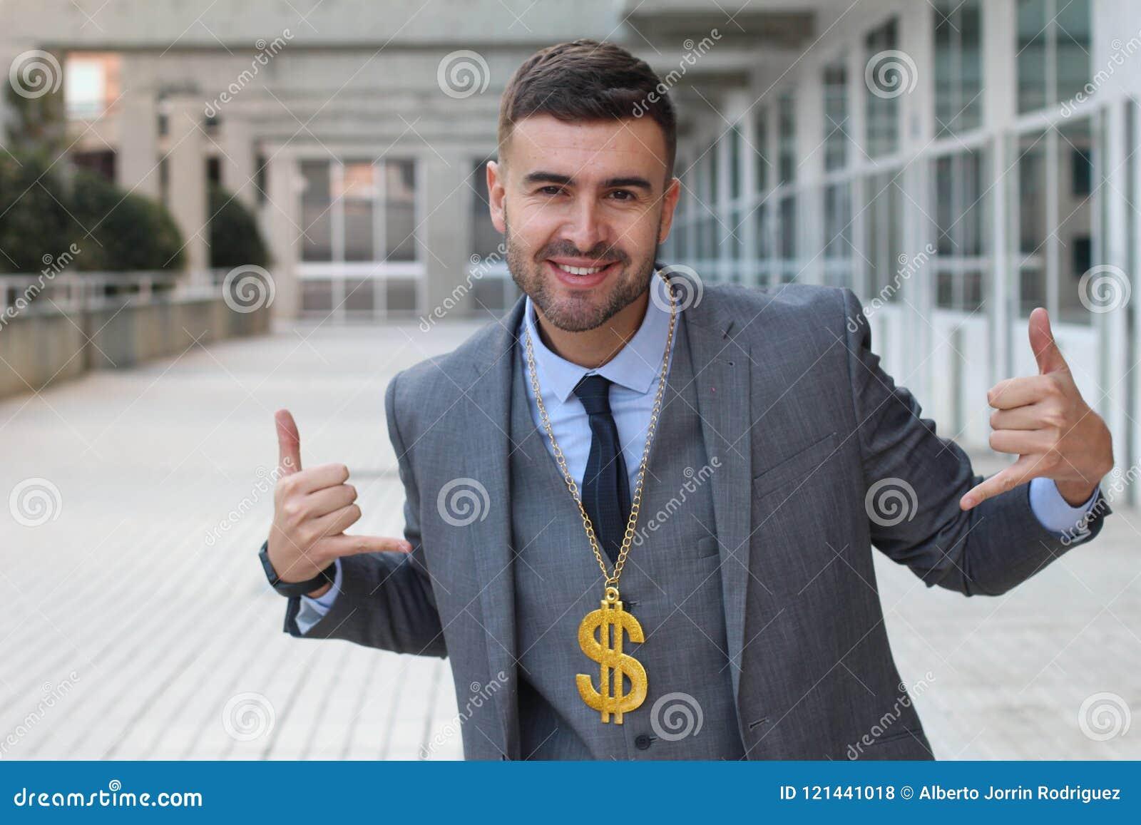 Affärsman som vaggar den guld- halsbandet med dollartecknet