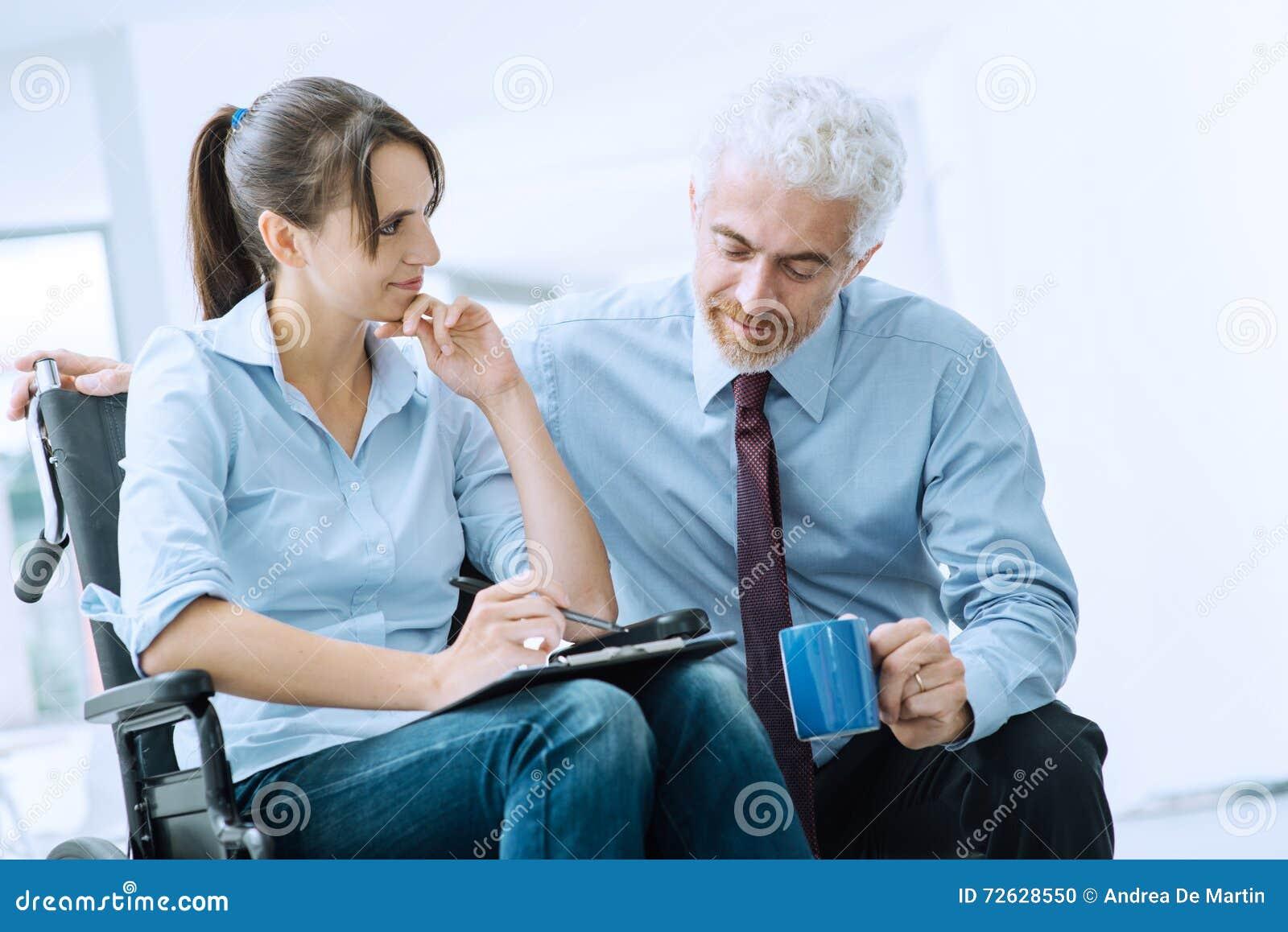 Affärsman som visar ett dokument till en kvinna i rullstol