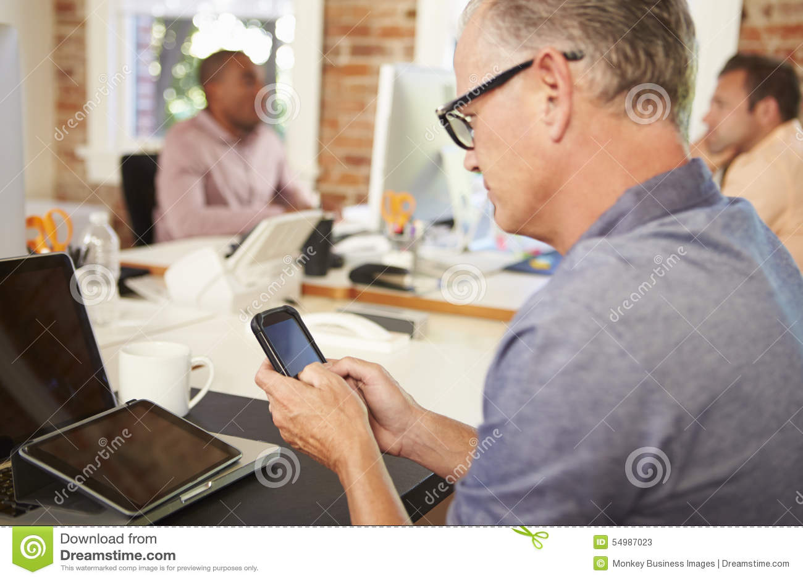 Affärsman Using Mobile Phone i idérikt kontor