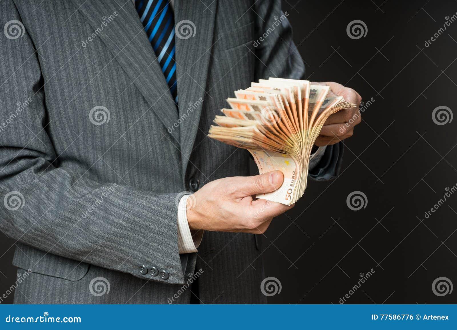 Affärsmannen är hållande kassa, fanen av femtio euro Personen räknar pengar Affärsmanhänder och euroräkningar