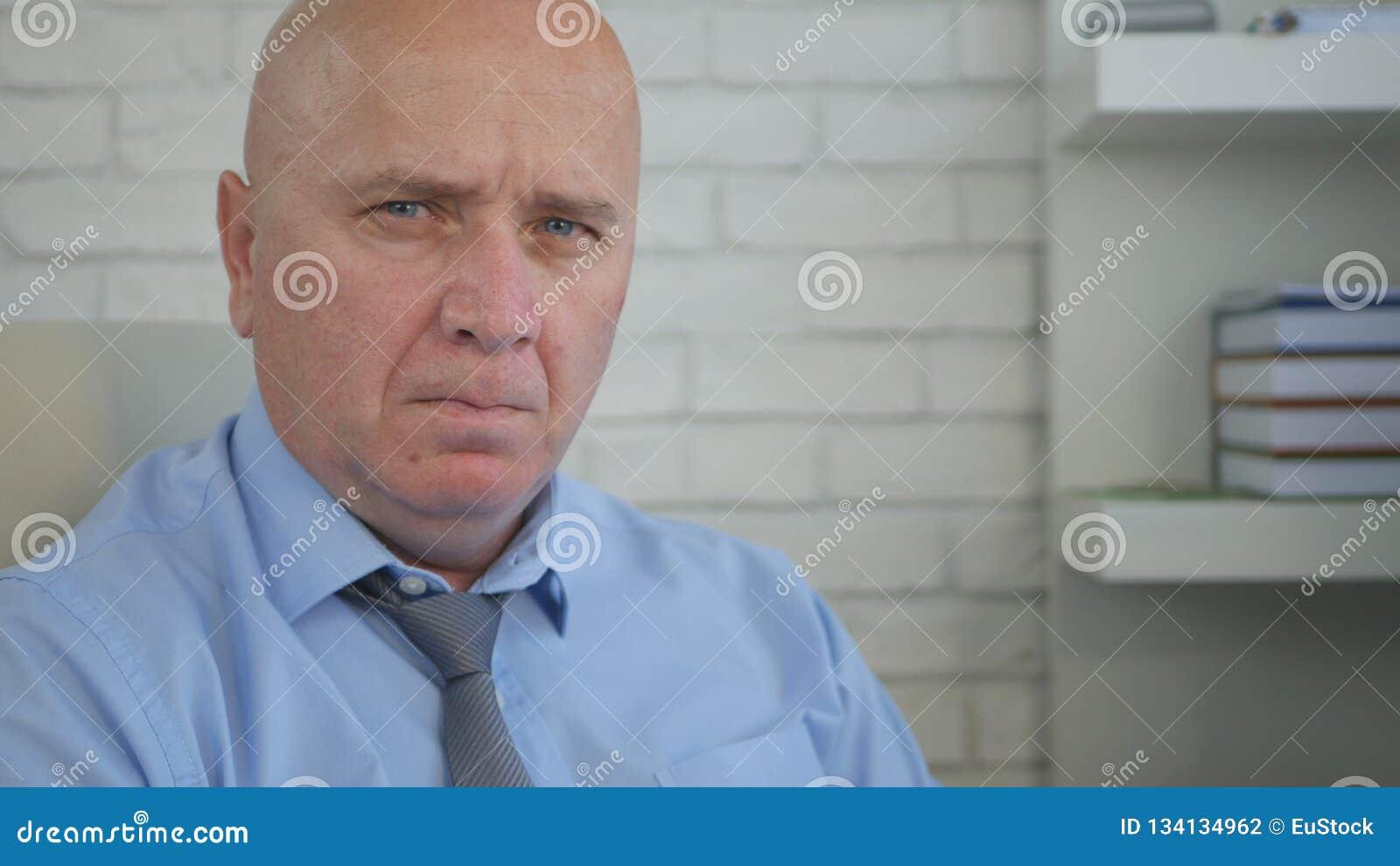 Affärsmannen avbildar i regeringsställning dåligt inre se till kameran som har en dålig blick