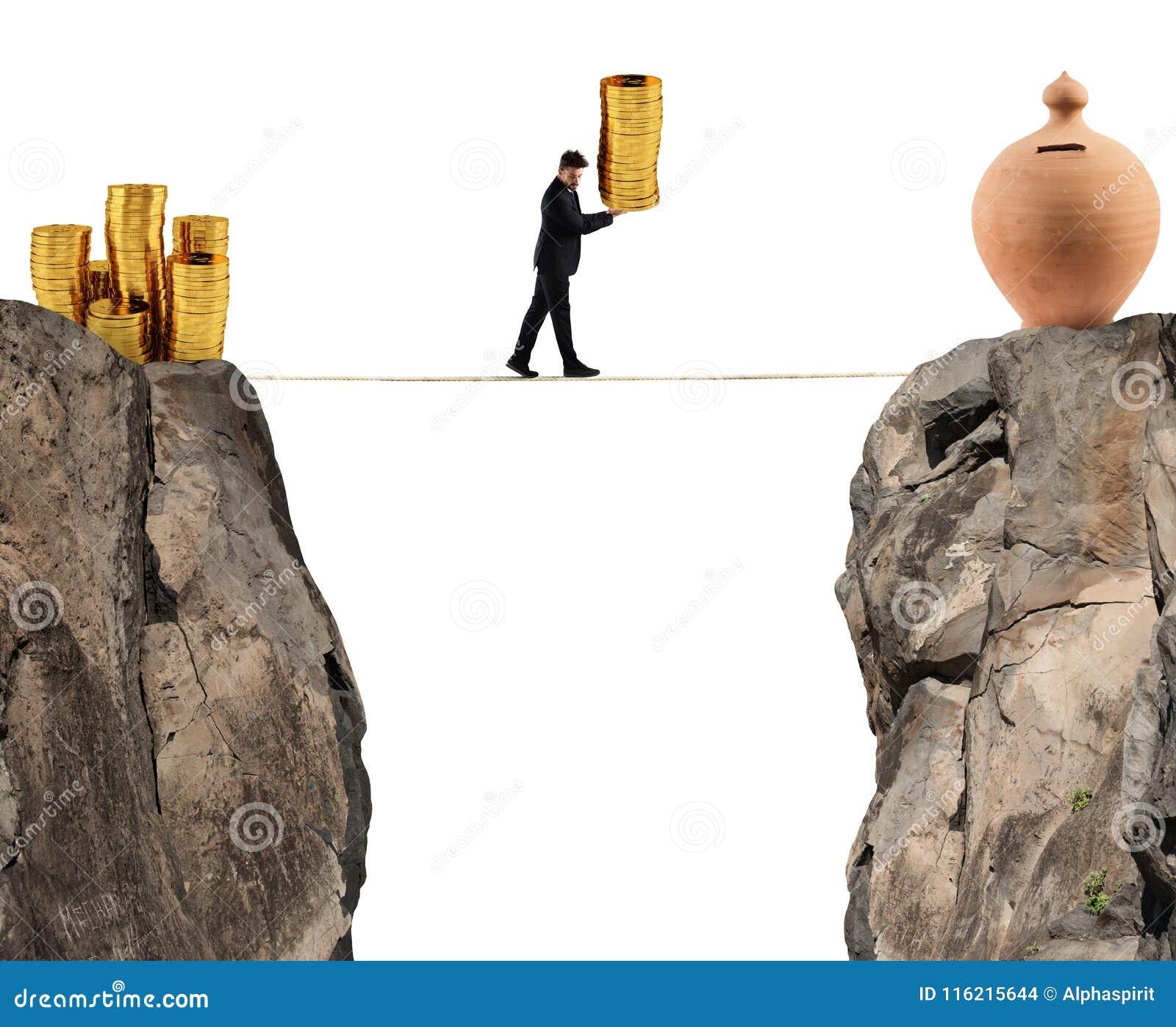 Affärsmannen flyttar en hög av mynt till en moneybox begrepp av sparande pengar för svårighet