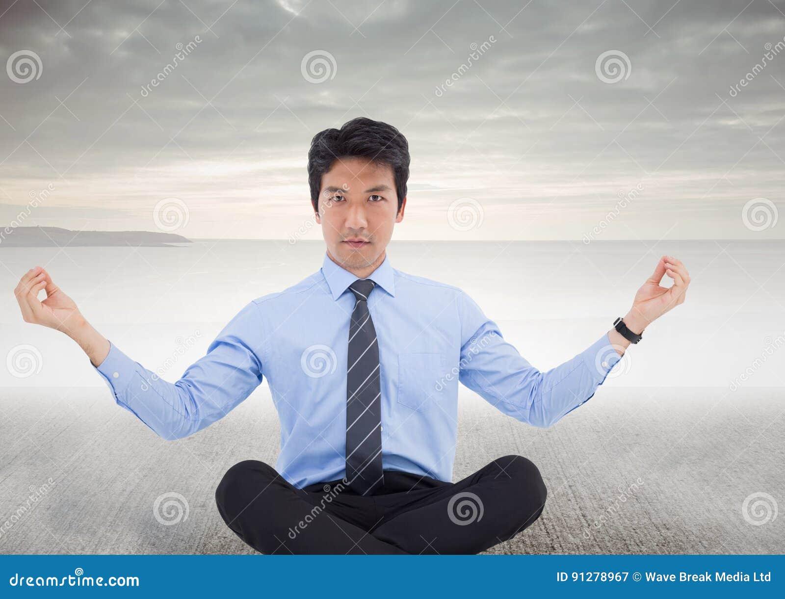 Affärsmannen som mediterar på betong, grundar mot grå himmel