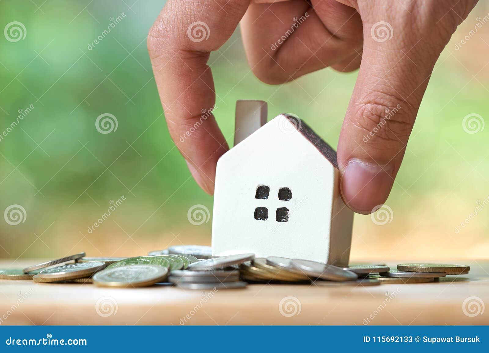 Affärsmannen som rymmer en modellhusmodell, förläggas på en hög av mynt använda som bakgrundsaffärsidé och fastighetbegrepp