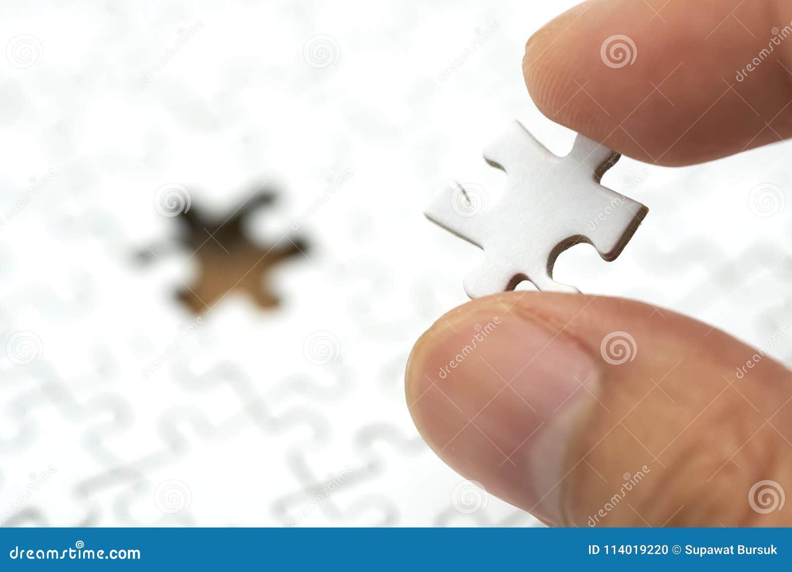 Affärsmannen som rymmer en vit figursåg, förläggas på en vit figursåg använda som bakgrundsaffärsidé och strategibegrepp med kopi