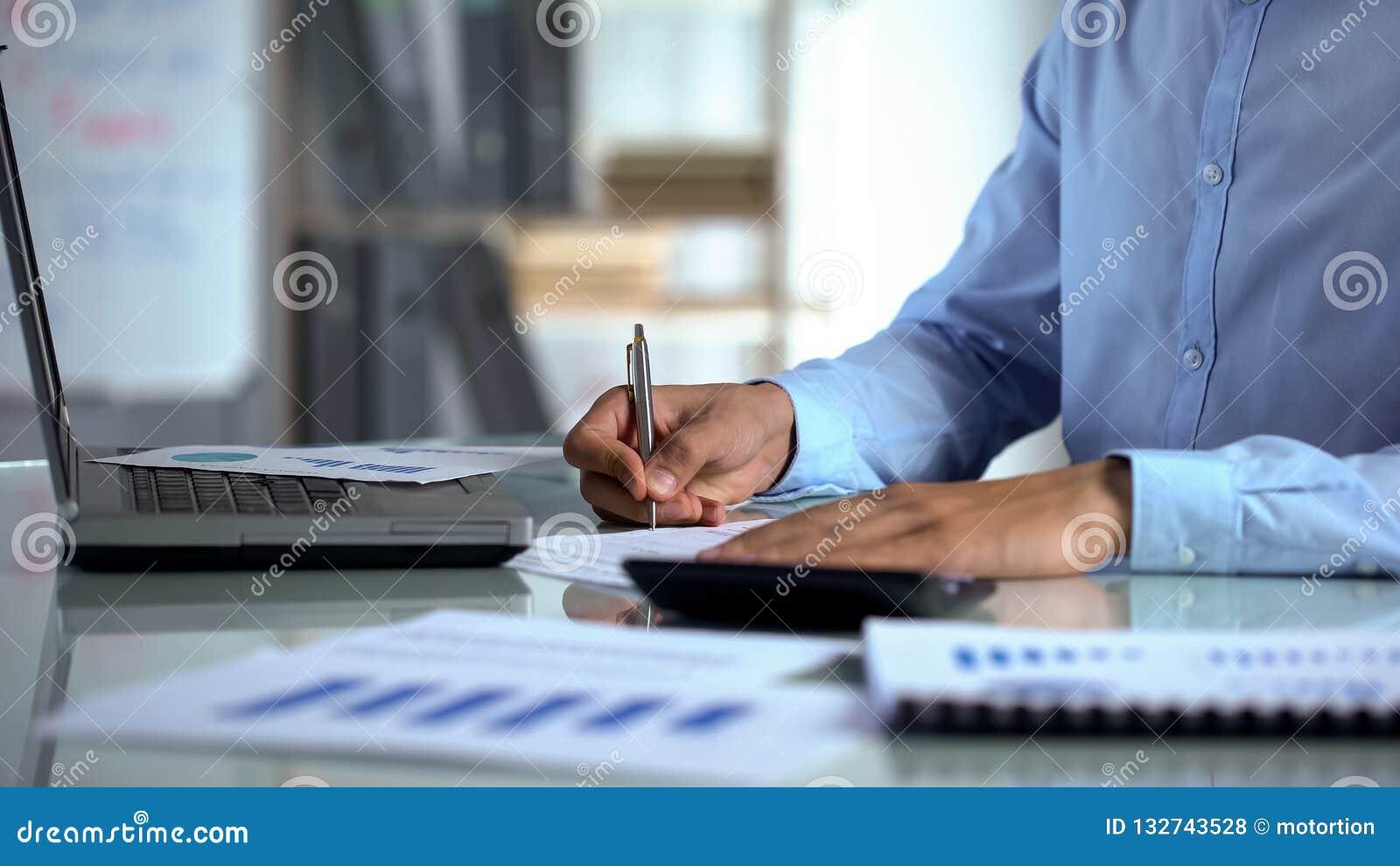 Affärsmanrevisor som använder räknemaskinen och fyller rapporten nära bärbara datorn på kontoret