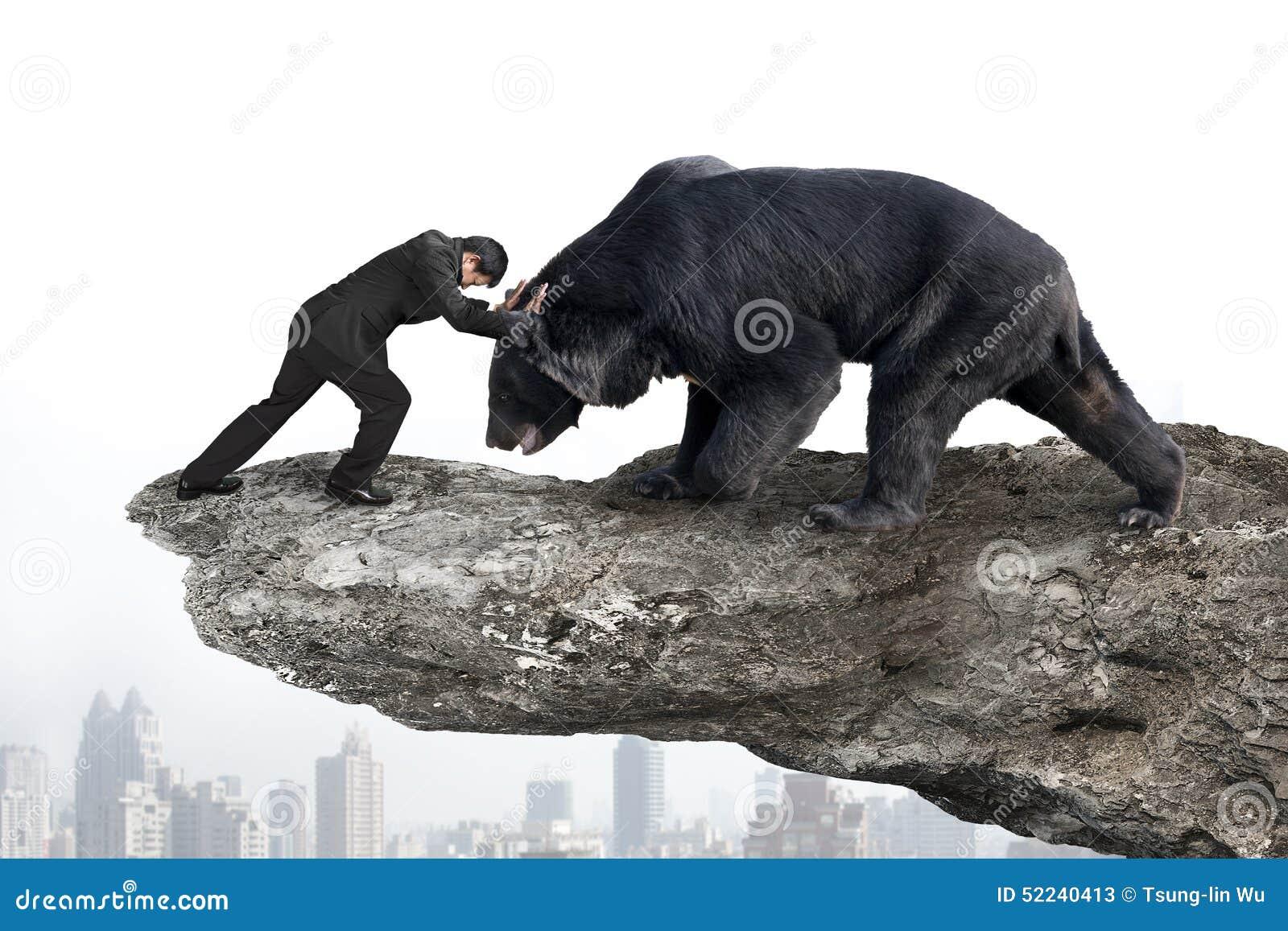 Affärsmanstridighet mot svart björn på klippan med himmelcitysc