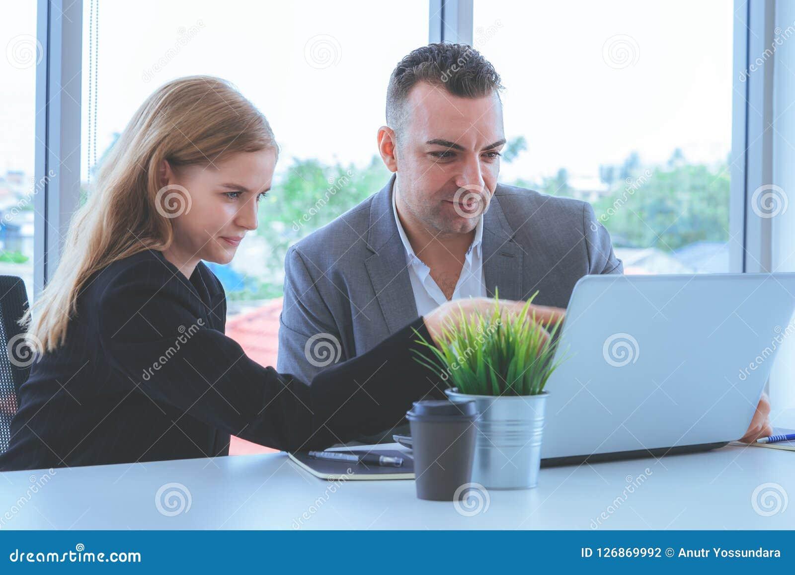 Affärspar som diskuterar på bärbar datorskärmen, Coworkerbrainst