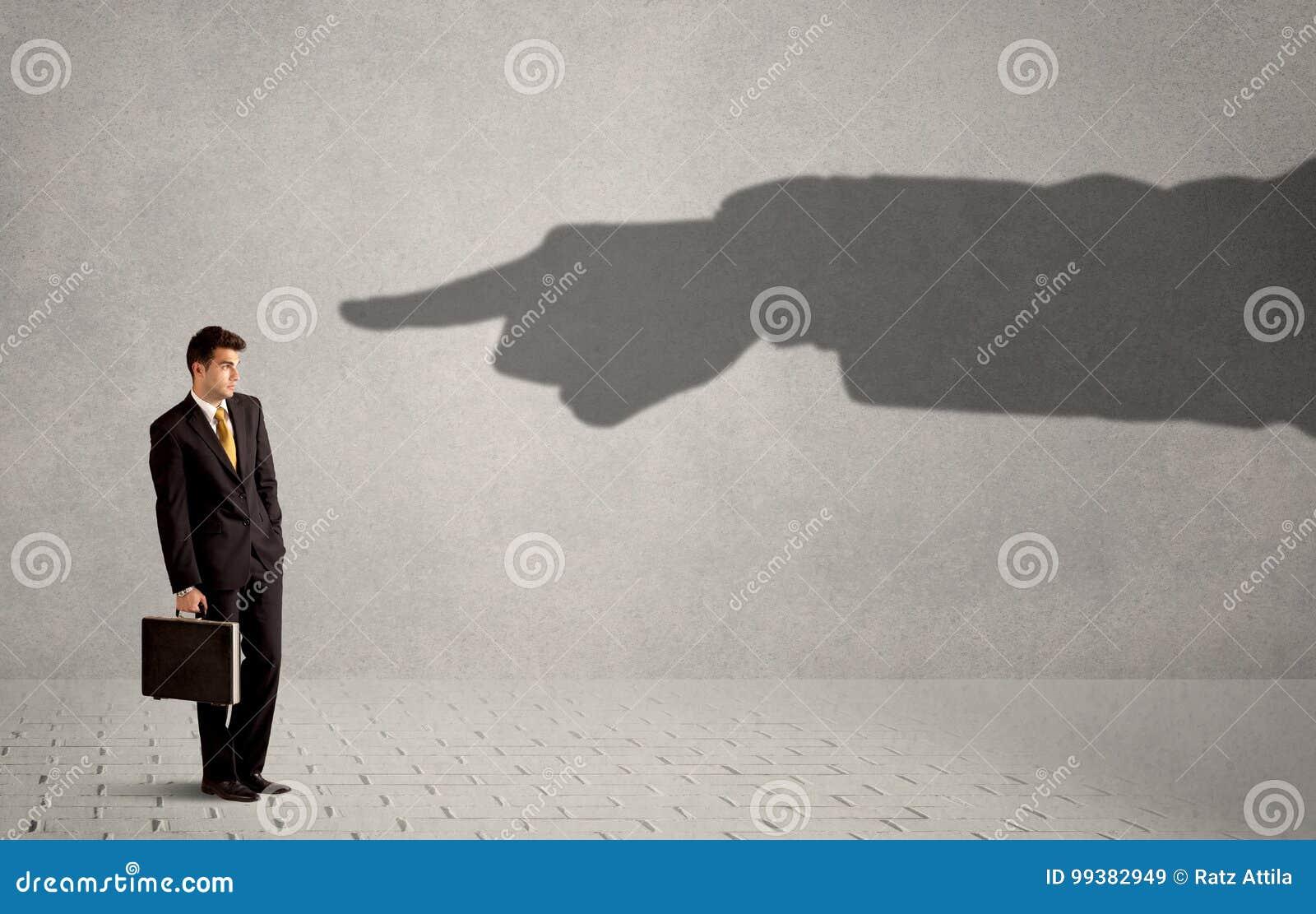 Affärsperson som ser den enorma skuggahanden som pekar på honom som är conc