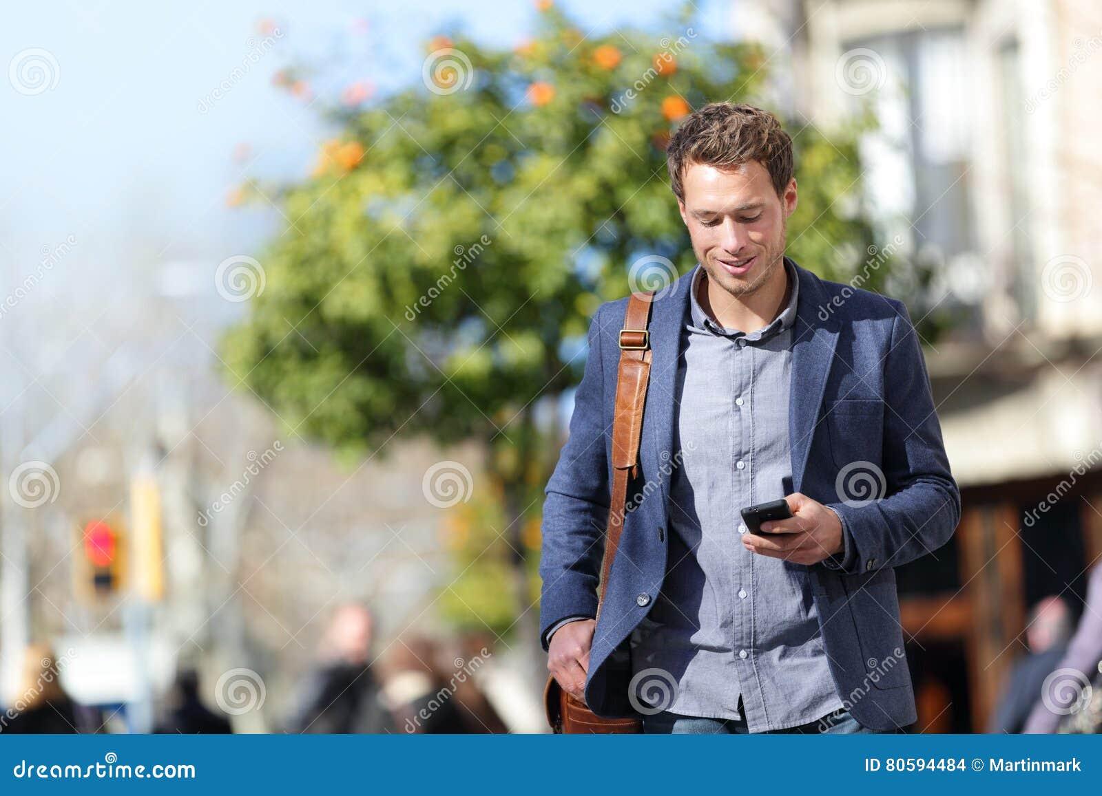 Affärspersonman på mobiltelefonen i stadsgata