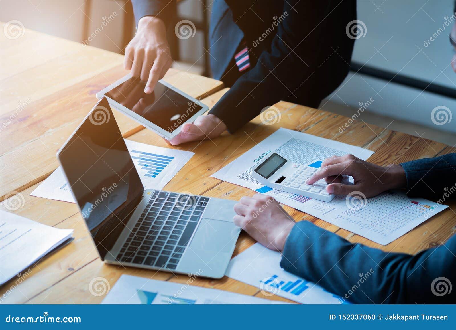 Aff?rslagg?va Det unga affärsfolket har möte och att arbeta i modernt kontor Bärbar dator, minnestavla och dokument på ett arbete