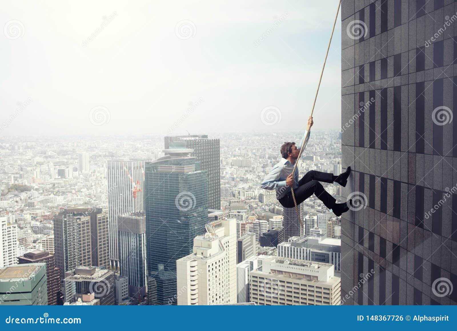 Aff?rsmannen kl?ttrar en byggnad med ett rep Begrepp av beslutsamhet