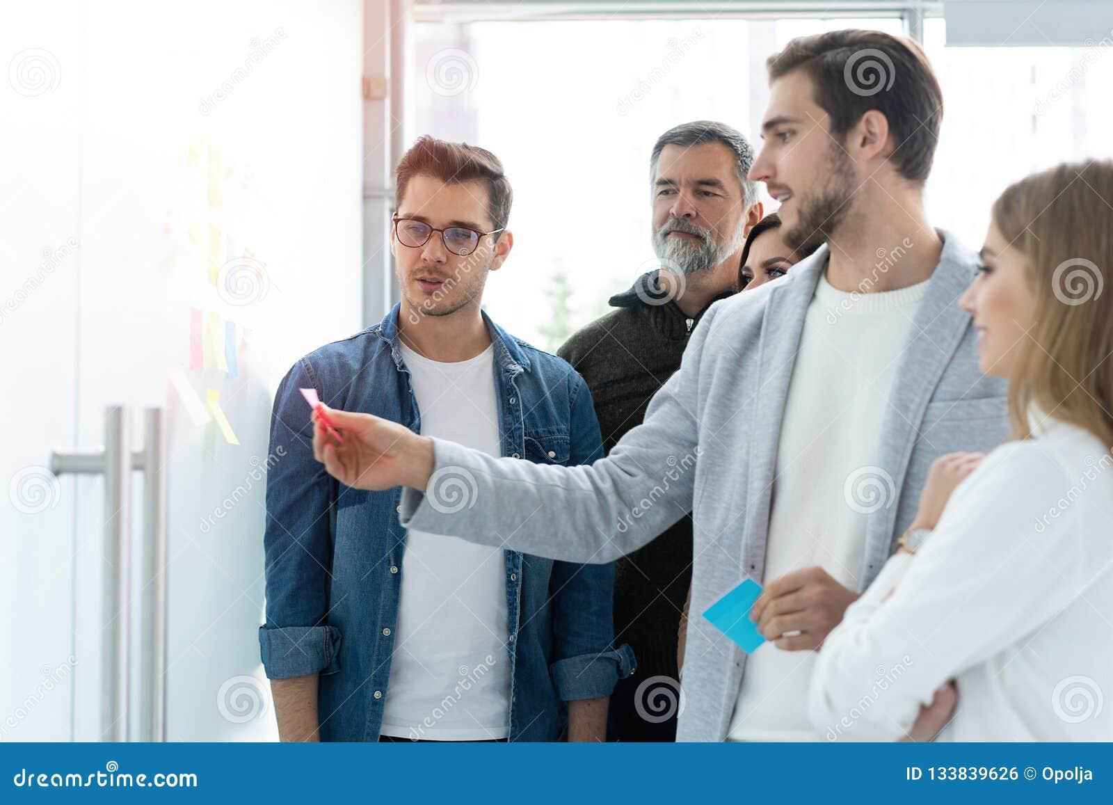 Affaires, éducation et concept de bureau - équipe d affaires avec le conseil de secousse dans le bureau discutant quelque chose