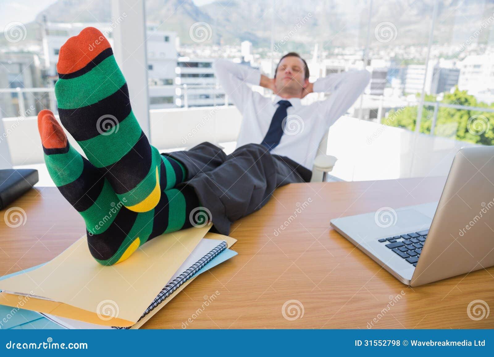 Affaires ayant un petit somme avec des pieds sur son bureau photo