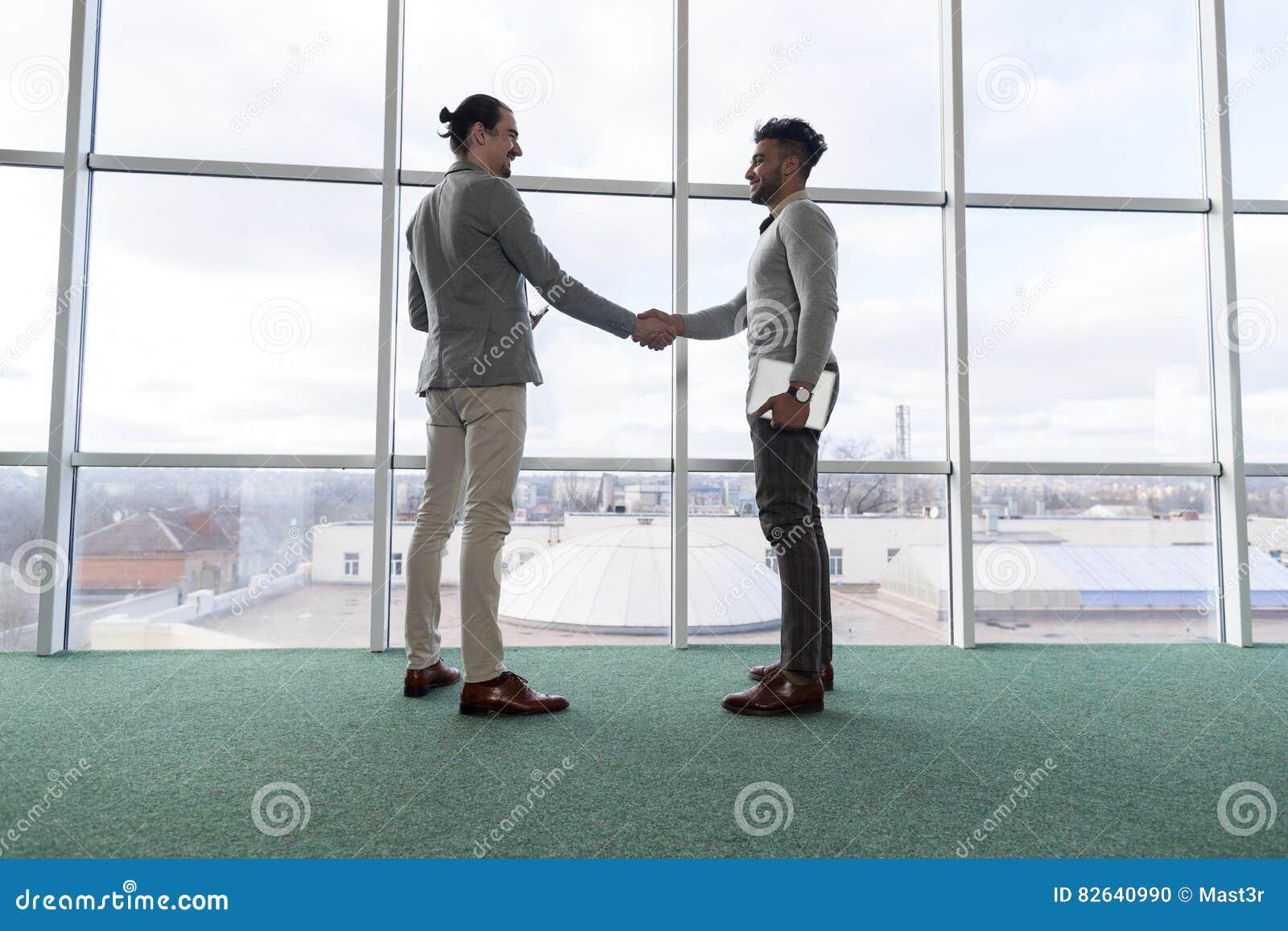 Affare Team Coworkers Stand del centro di Coworking di accordo della mano di scossa dell uomo di affari due in grande finestra pa