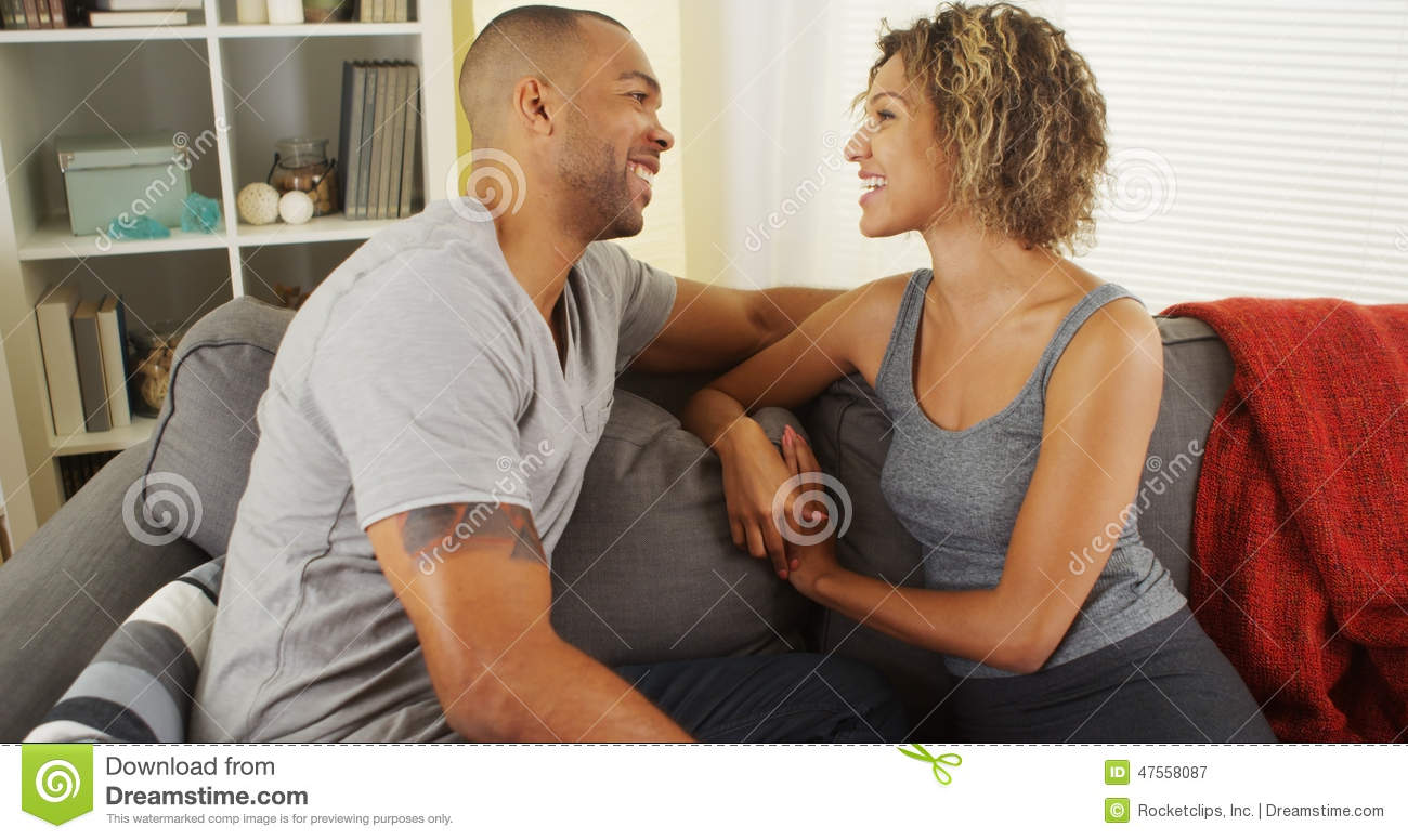 Affectionate black couple talking on couch