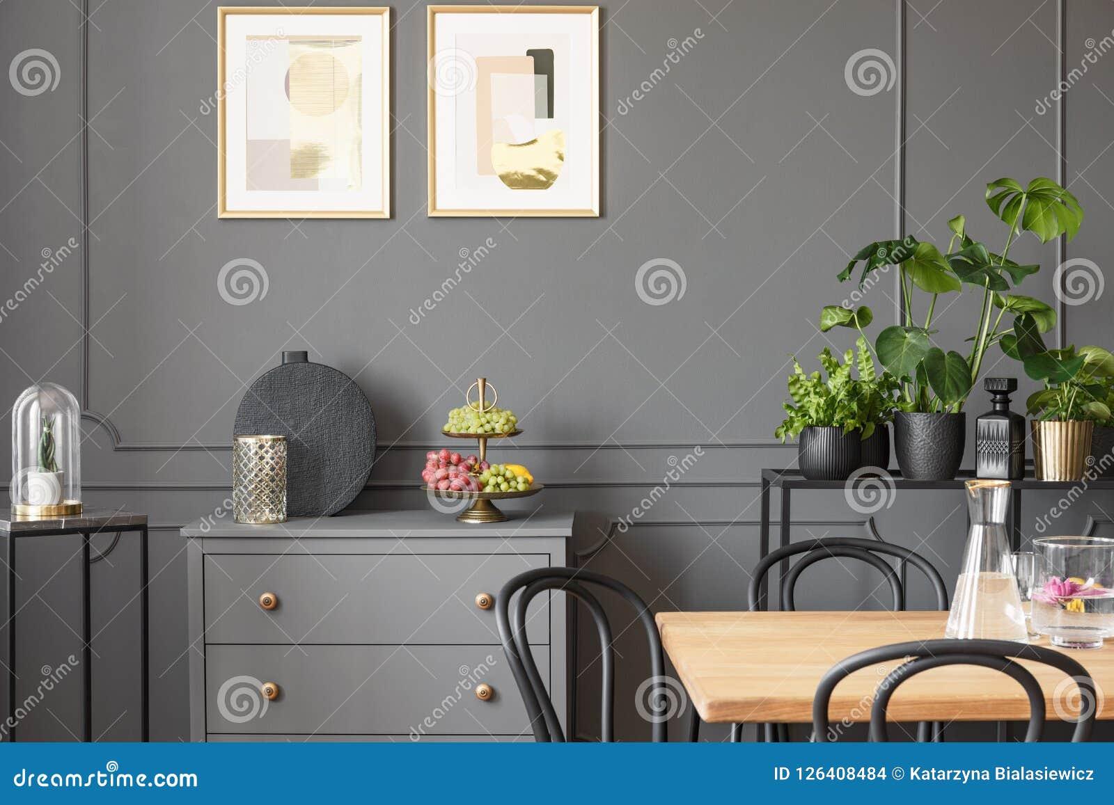 Affiches boven grijs kabinet in donker eetkamerbinnenland met pla