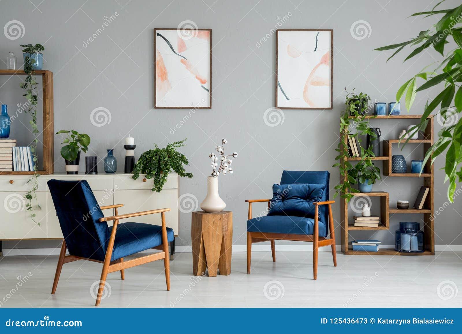 Affiches en installaties in helder woonkamerbinnenland met marineblauwe leunstoelen en bloemen Echte foto