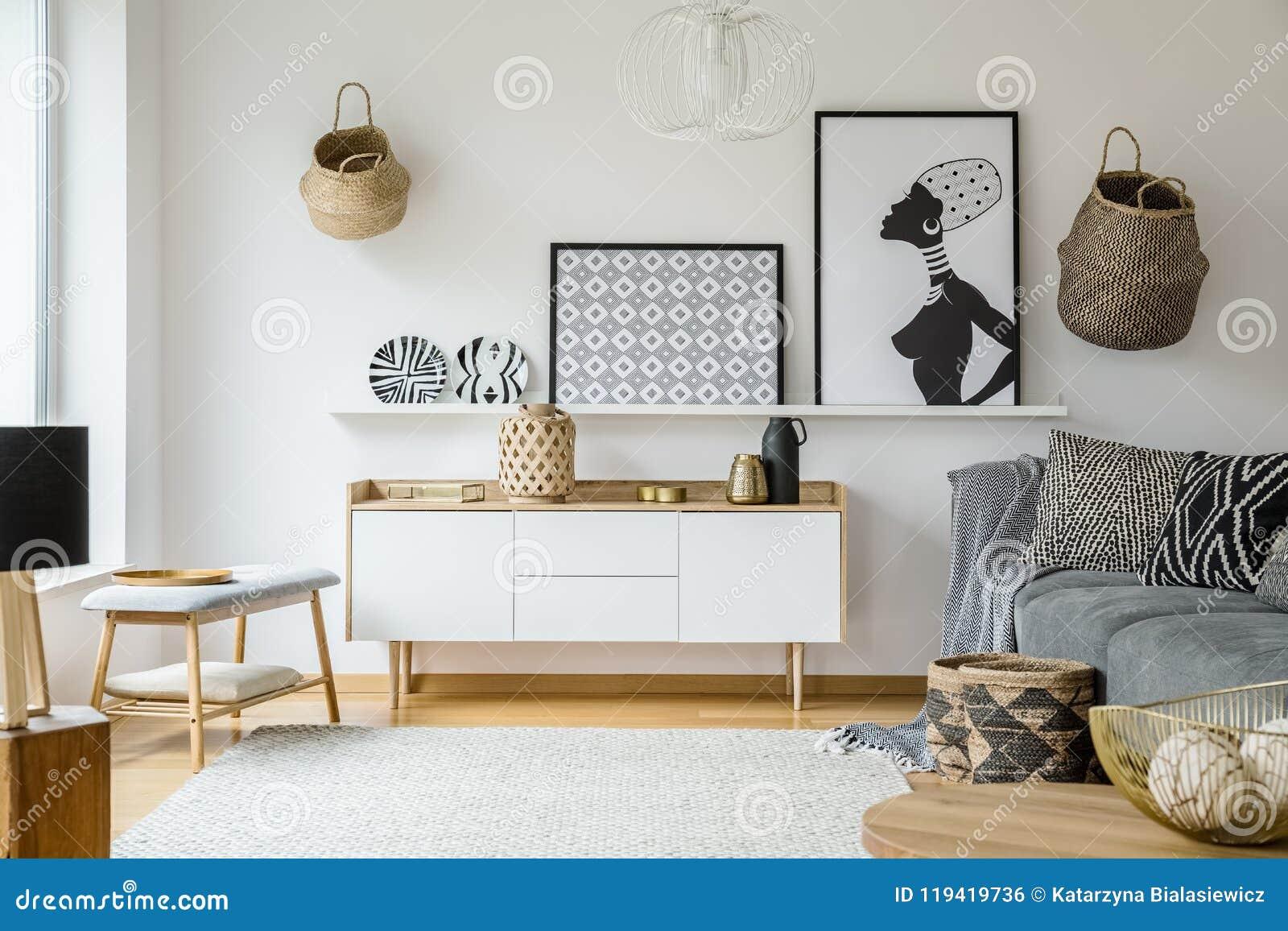 Affiches en platen boven houten kast in bohowoonkamer int.