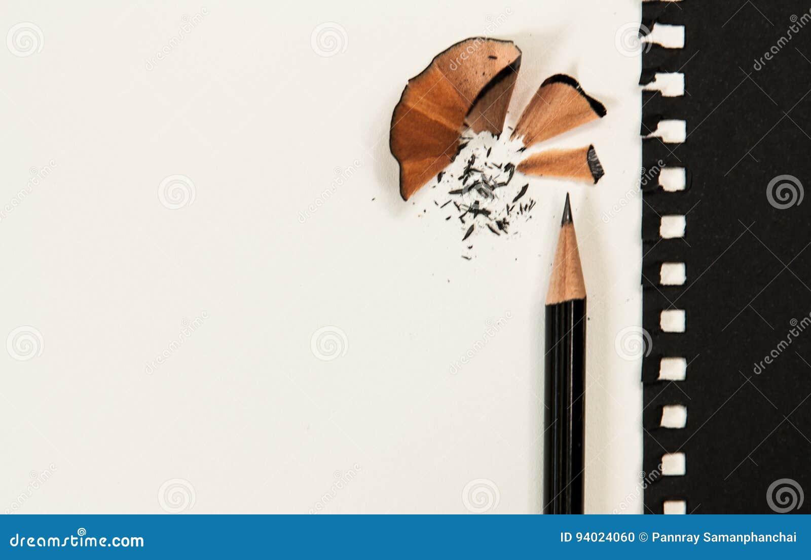 Affili la matita sullo scrittorio bianco Oltre alla carta nera