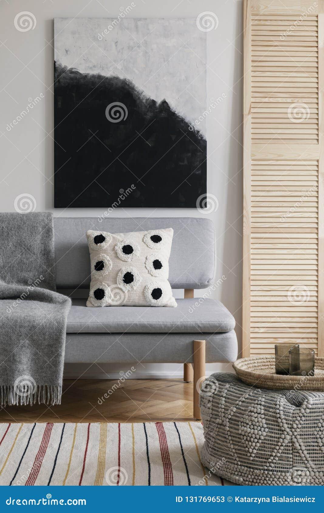 Affisch ovanför grå soffa med den mönstrade kudden i naturlig vardagsruminre Verkligt foto