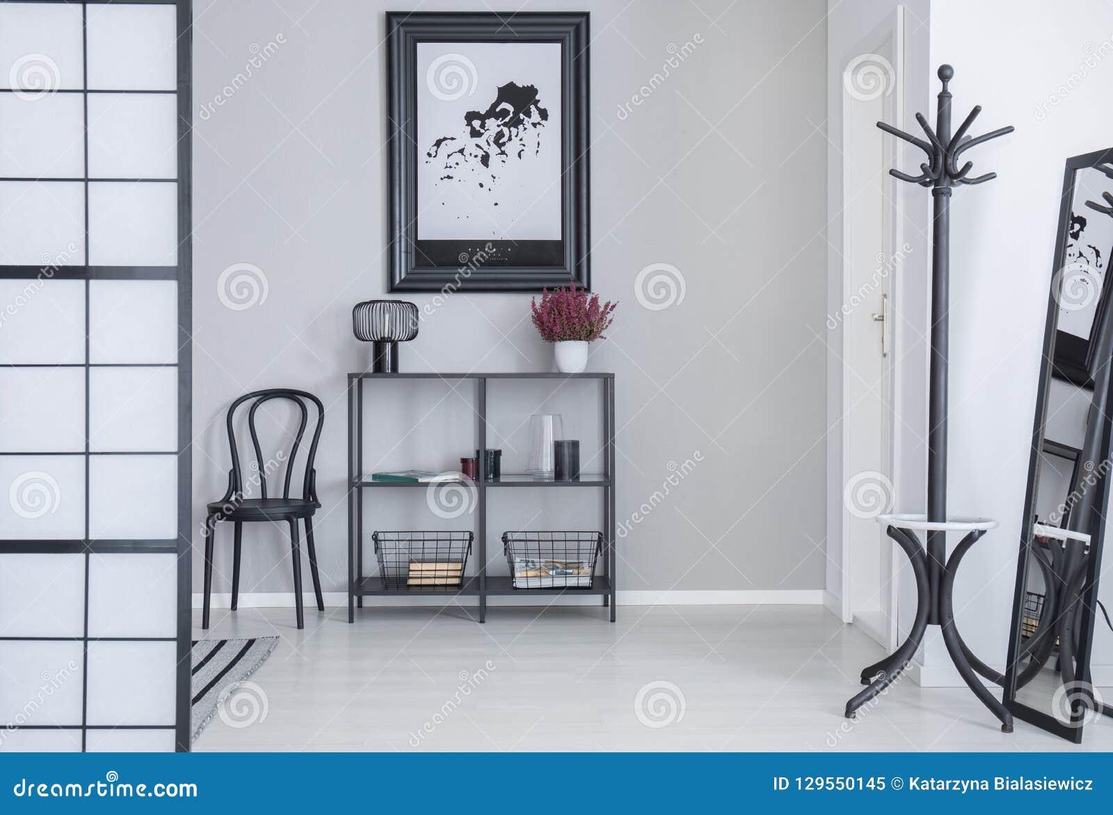 Affisch ovanför hyllor med blommor och lampan i den vita enkla korridorinre med kuggen och svart stol