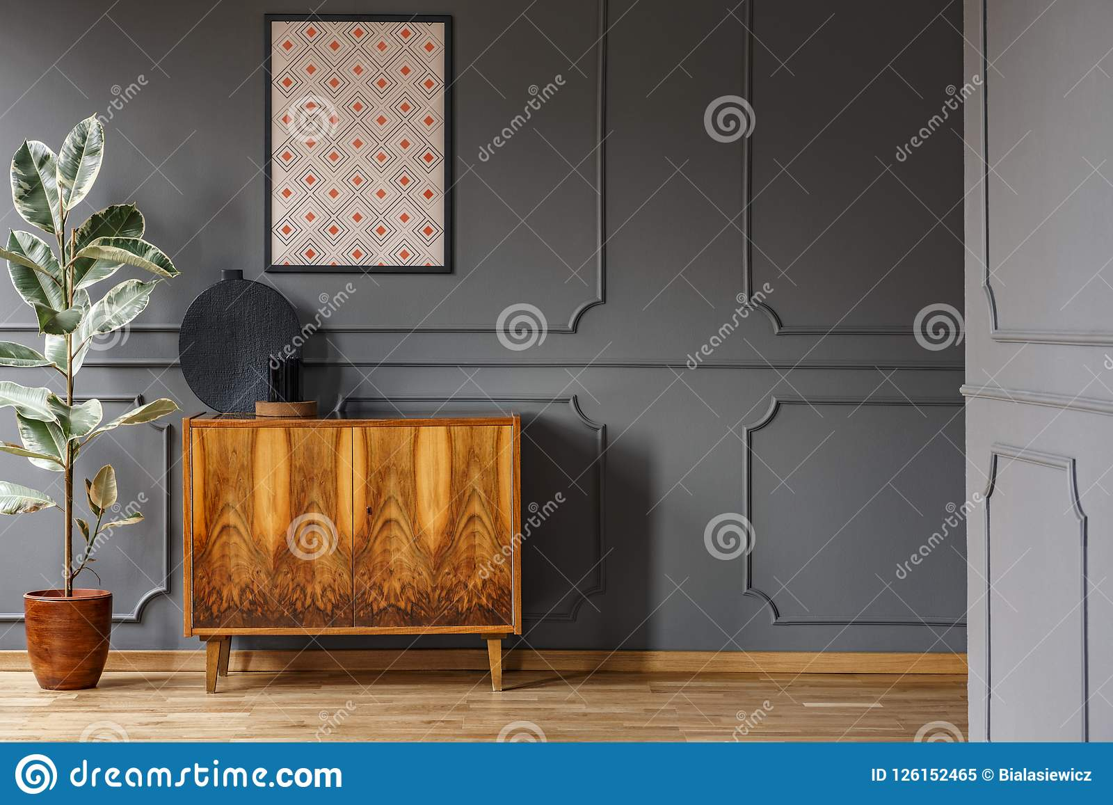 Affisch ovanför träkabinettet bredvid fikus i vardagsruminterio